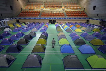Man walks amidst tents set up on the floor of a gymnasium for parents of freshmen students at Tianjin University in Tianjin municipality