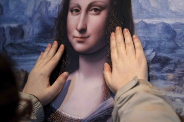 """A visually impaired visitor touches a work representing Leonardo da Vinci's Mona Lisa, at an exhibition called """"Touching the Prado"""" at the Prado museum in Madrid"""