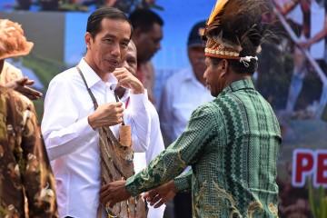 Presiden Joko Widodo dikalungi tas noken khas Papua setelah melakukan peletakan batu pertama (groundbreaking) untuk fasilitas PON 2020 di Jayapura, Papua, Sabtu (9/5). Pembangunan fasilitas olahraga untuk even Pekan Olahraga Nasional (PON) 2020 itu diperkirakan menelan anggaran Rp10 triliun.  ANTARA FOTO/Hafidz Mubarak A./ed/mes/15