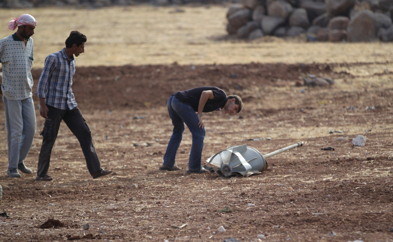 Beberapa pria memeriksa sisa roket yang menurut aktivis ditembakkan oleh angkatan udara Rusia di kota Maasran, di selatan kota Idlib, Suriah, Rabu (7/10). ANTARA FOTO/REUTERS/Khalil Ashawi.