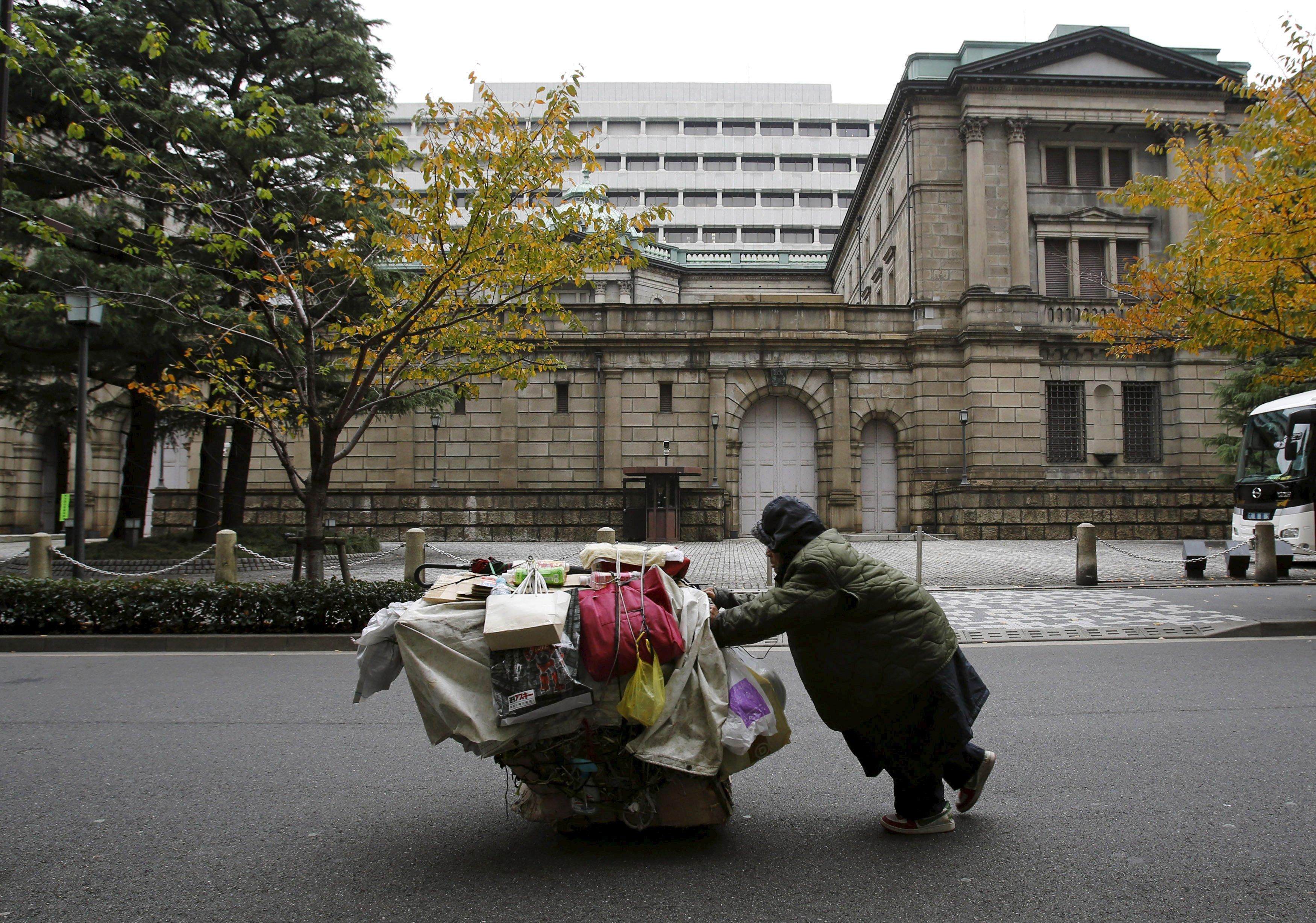 Seorang pria mendorong troli berisi barang miliknya di luar kantor pusat Bank of Japan (BOJ) di Tokyo dalam arsip foto  26 November 2012. Bank of Japan akan memotong angka pertumbuhan dan prospek inflasi untuk tahun anggaran ini direview minggu depan tapi hanya sedikit mengenai proyeksi tahun depan, menurut sebuah sumber, yang mungkin akan menegaskan bahwa bank sentral akan memudahkan kebijakan moneter selanjutnya. ANTARA FOTO/REUTERS/Yuriko Nakao.