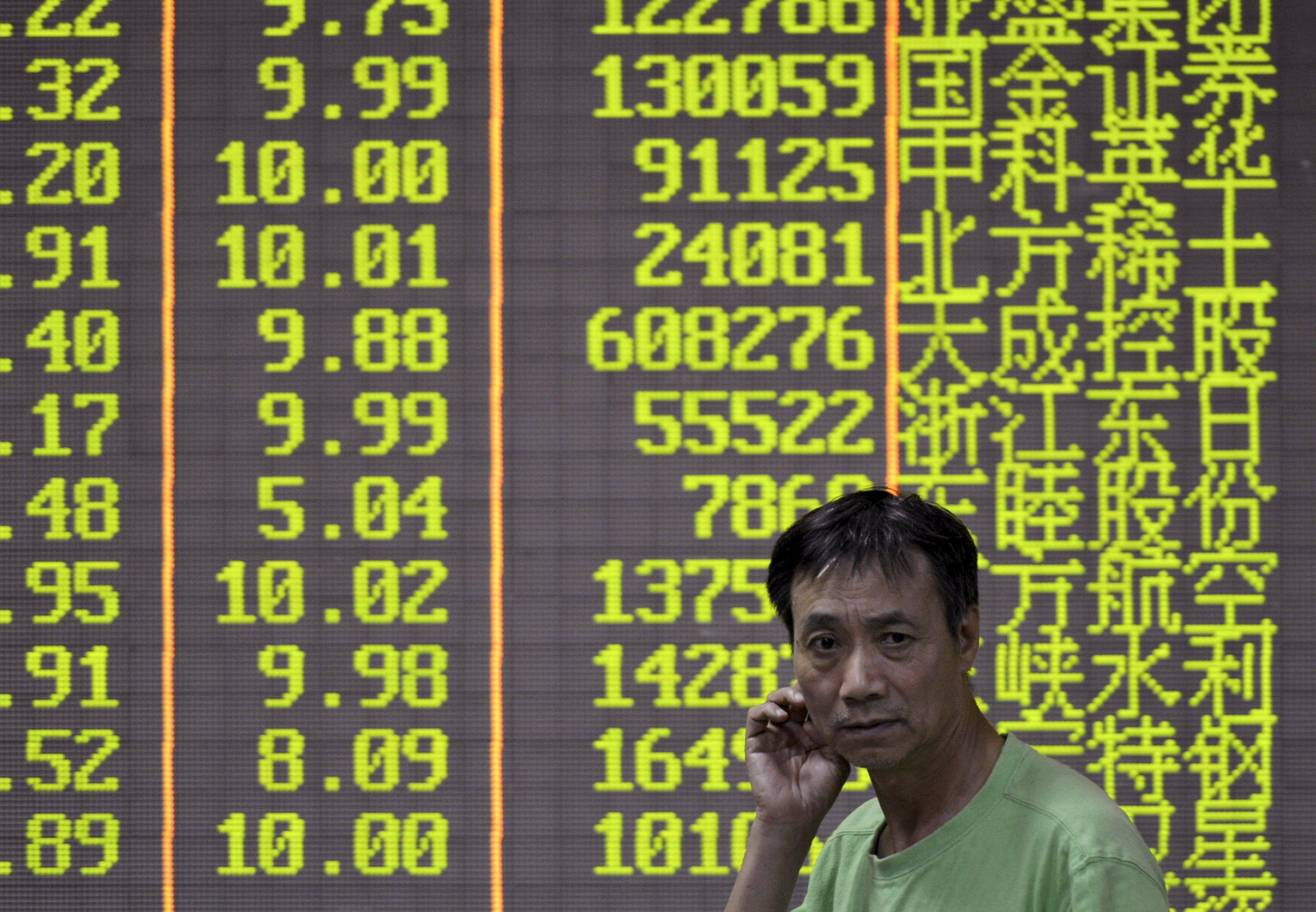 Seorang investor berjalan di depan layar informasi saham di bursa saham di Hangzhou, Provinsi Zheijang, Tiongkok, Rabu (21/10). Indeks acuan Tiongkok merosot hingga 3 persen pada hari Rabu dalam performa harian terburuk mereka selama lima minggu sementara koreksi kecil semakin dalam pada hari itu, memicu penjualan saham pada sore hari ke pasar yang lebih luas. ANTARA FOTO/REUTERS/Stringer.