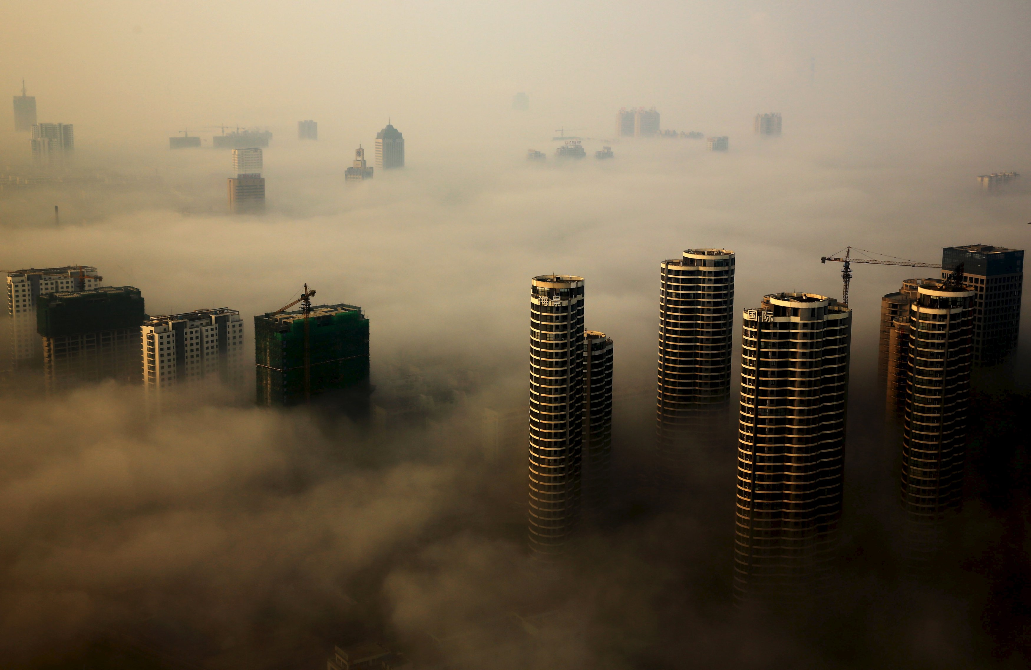 Gedung yang masih dalam konstruksi terlihat di antara kabut saat hari berkabut di Rizhao, Provinsi Shandong, Tiongkok, 18 Oktober 2015. ANTARA FOTO/REUTERS/Stringer.