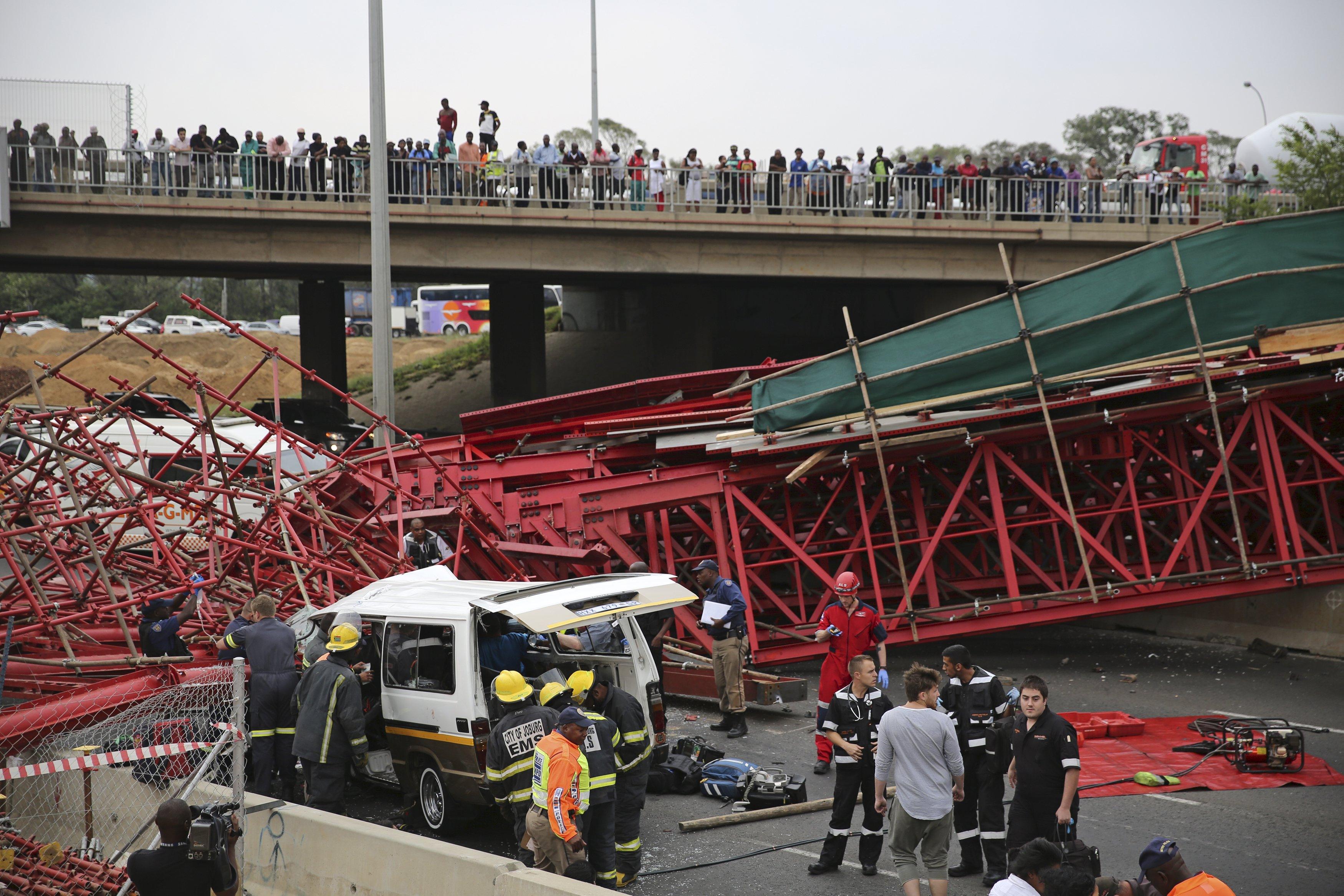 Pejalan kaki melihat paramedis berusaha mengeluarkan penumpang dari sebuah taksi ketika jembatan di jalan layang M1 roboh dekat jalan keluar menuju Sandton, Afrika Selatan, Rabu (14/10). Satu orang tewas dan 17 lainnya mengalami cedera ketika sebuah jembatan roboh di atas jalan utama Johannesburg kemarin, menurut petugas gawat darurat setempat. Reruntuhan jembatan baja kusut berwarna merah melintang di tengah jalan layang M1 Johannesburg, dekat jalan keluar menuju Sandton, lokasi gedung bursa saham, menambah kekacauan lalu lintas jam-sibuk. ANTARA FOTO/REUTERS/Siphiwe Sibeko.