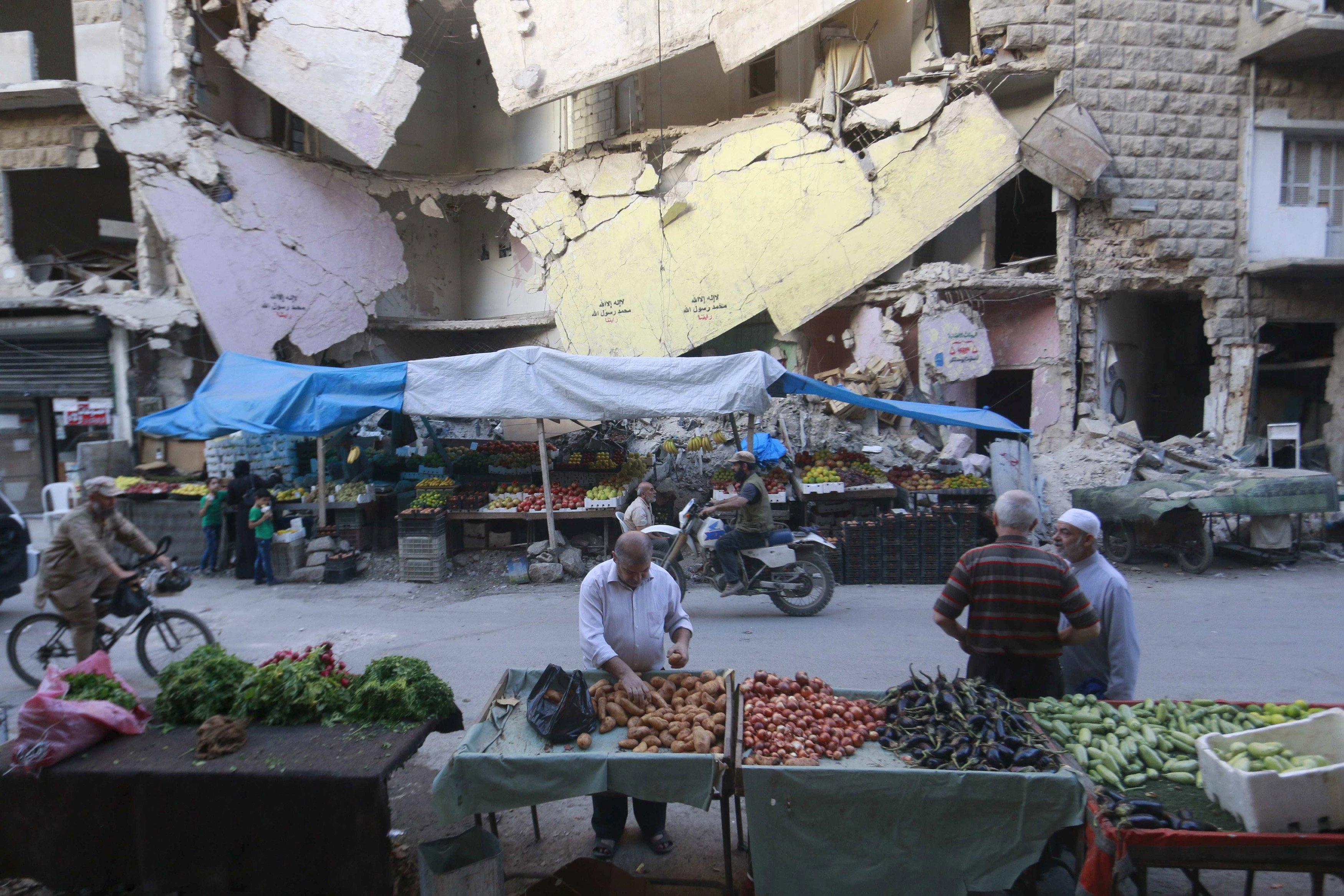 Warga berbelanja sayuran dan buah-buahan yang dijual di depan gedung rusak di wilayah Bustan al-Qasr, Aleppo, Suriah, Rabu (14/10). ANTARA FOTO/REUTERS/Hosam Katan.