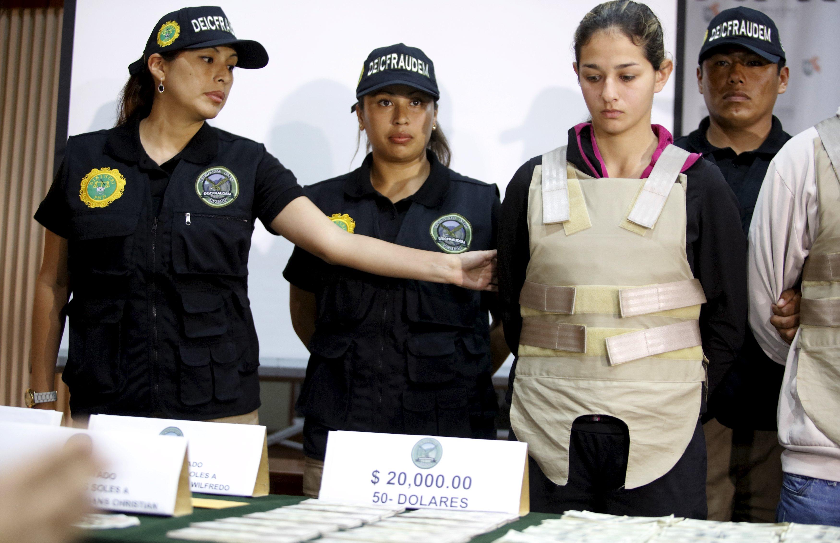 Petugas kepolisian menunjukkan Isabel Mendoza Poma (kanan), yang tertangkap saat polisi menyita dolar AS palsu, dalam konferensi pers di Lima, Rabu (14/10). Polisi Nasional menyita dolar palsu senilai USD 836.000 yang dimasukkan ke dalam tas dan tas punggung dengan tujuan New York, Amerika Serikat, menurut keterangan siaran pers polisi. ANTARA FOTO/REUTERS/Guadalupe Pardo.