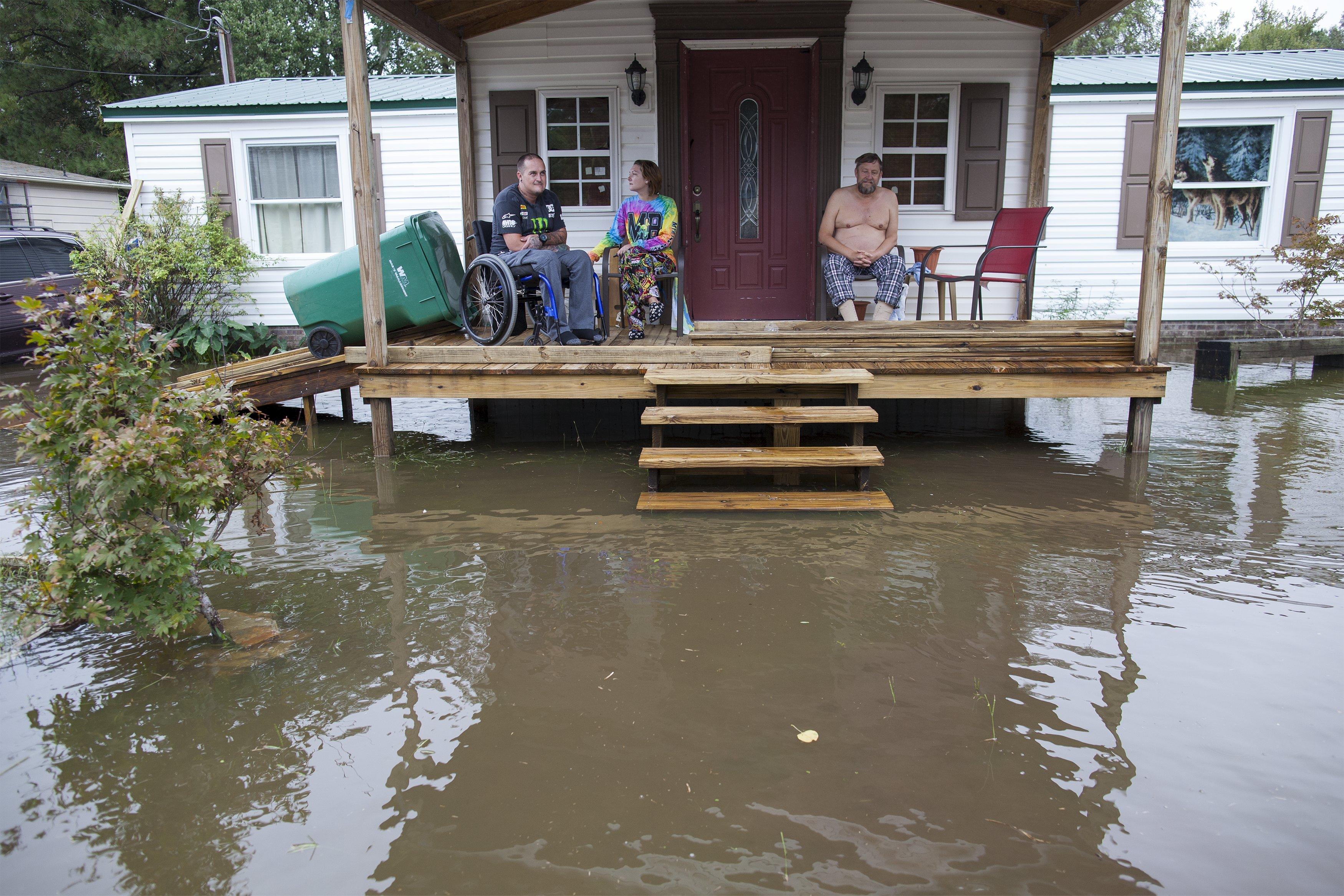 Chris Stumbo (kiri-kanan), kekasihnya Felicia Howerton dan Paul Stumbo memantau tinggi air banjir yang mengepung rumah mereka di Applewood Court di Myrtle Beach, Carolina Selatan, Senin (5/10). Hujan lebat yang menurut gubernur Carolina Selatan hujan-sekali-seabad menyebabkan banjir di negara bagian tenggara Amerika Serikat kemarin, dan menewaskan delapan jiwa di Carolinas. ANTARA FOTO/REUTERS/Randall Hill.