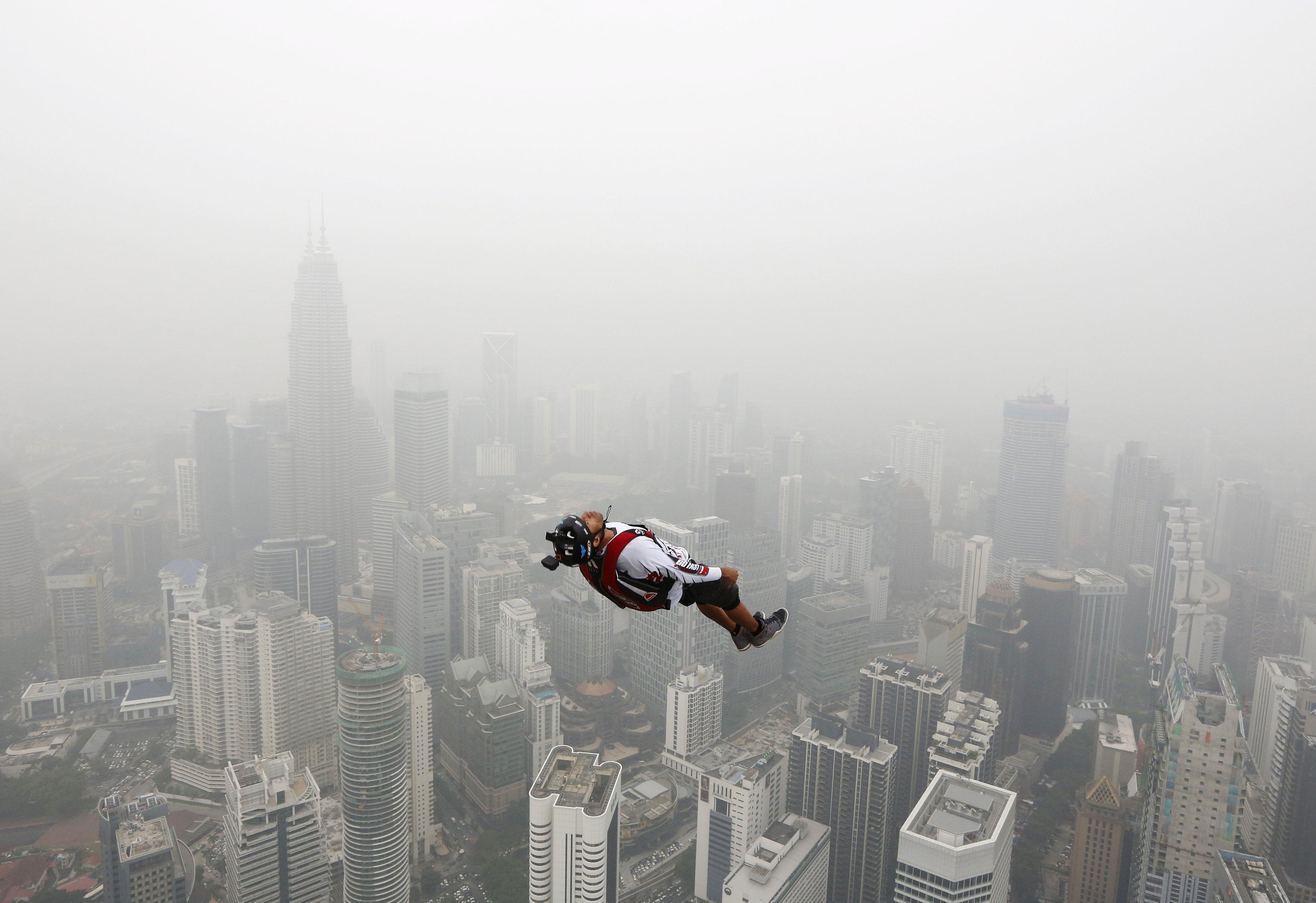 Penerjun BASE melompat dari Menara Kuala Lumpur setinggi 300 meter dalam acara Lompat Menara Internasional dengan lebih dari 100 orang ikut serta, di hari berkabut di Kuala Lumpur, Malaysia, Jumat (2/10). Penebangan dan pembakaran lahan untuk pertanian di wilayah Indonesia membuat Malaysia dan Singapura diselimuti kabut asap selama beberapa pekan. ANTARA FOTO/REUTERS/Olivia Harris.