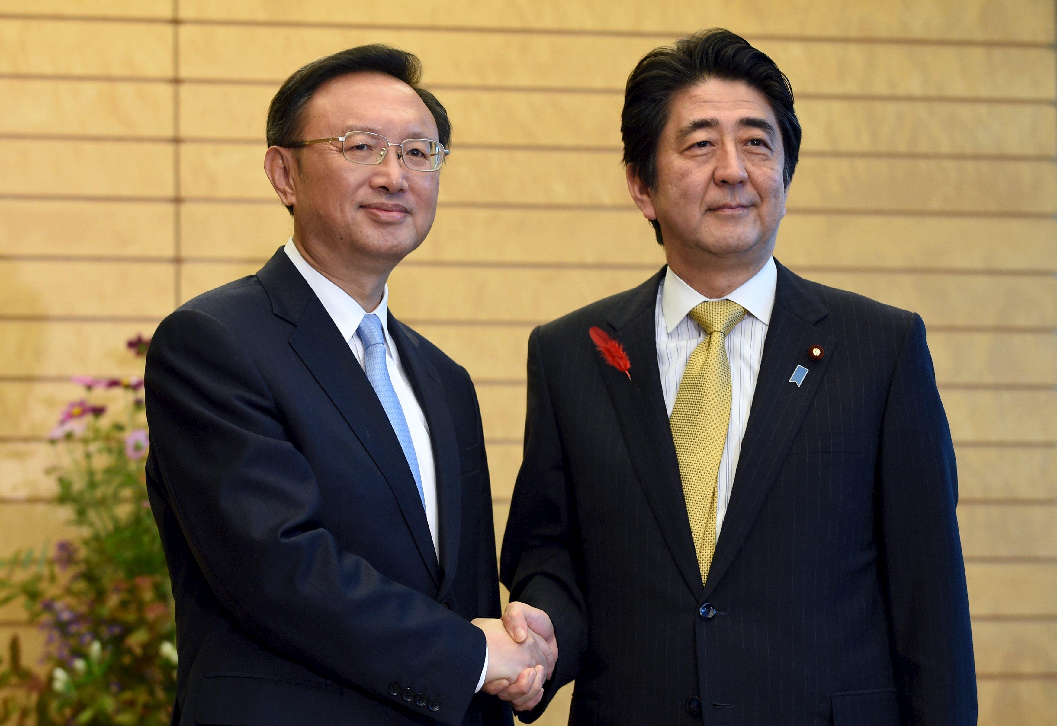 Anggota Dewan Nasional Tiongkok Yang Jiechi (kiri) bersalaman dengan Perdana Menteri Jepang Shinzo Abe pada awal pembicaraan di kediaman resmi Abe di Tokyo, 14 Oktober 2015. Pejabat senior Tiongkok dan Jepang pada hari Selasa sepakat untuk melakukan dialog tingkat tinggi untuk memperbaiki hubungan yang retak, kata pejabat pemerintah Jepang. Yang, diplomat top Tiongkok, dan Shotaro Yachi, Kepala Badan Keamanan Nasional Jepang, sepakat di Tokyo untuk mendorong dialog bilateral termasuk dialog antara pejabat tinggi, kata pejabat Jepang. ANTARA FOTO/REUTERS/Toshifumi Kitamura.