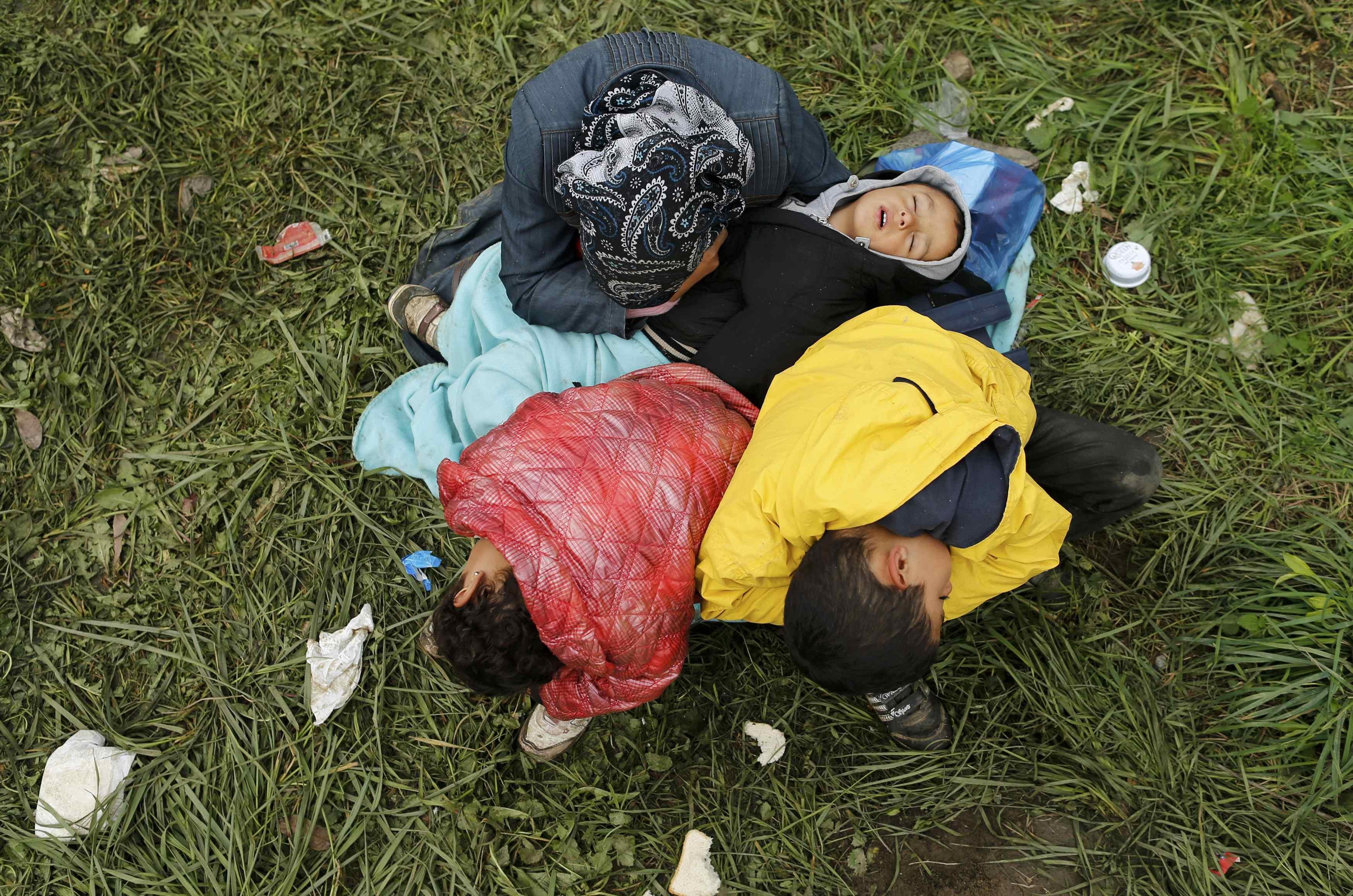 Seorang perempuan dan tiga orang anak berisitrahat  setelah migran menyeberangi perbatasan dari Kroasia dekat Rigonce, Slovenia, Rabu (21/10). Parlemen Slovenia meloloskan peraturan yang akan memberikan tentara kekuatan lebih untuk menolong polisi menjaga perbatasan negara saat ribuan migran memasuki negeri tersebut dari Kroasia setelah Hungaria menutup perbatasannya. ANTARA FOTO/REUTERS/Antonio Bronic.