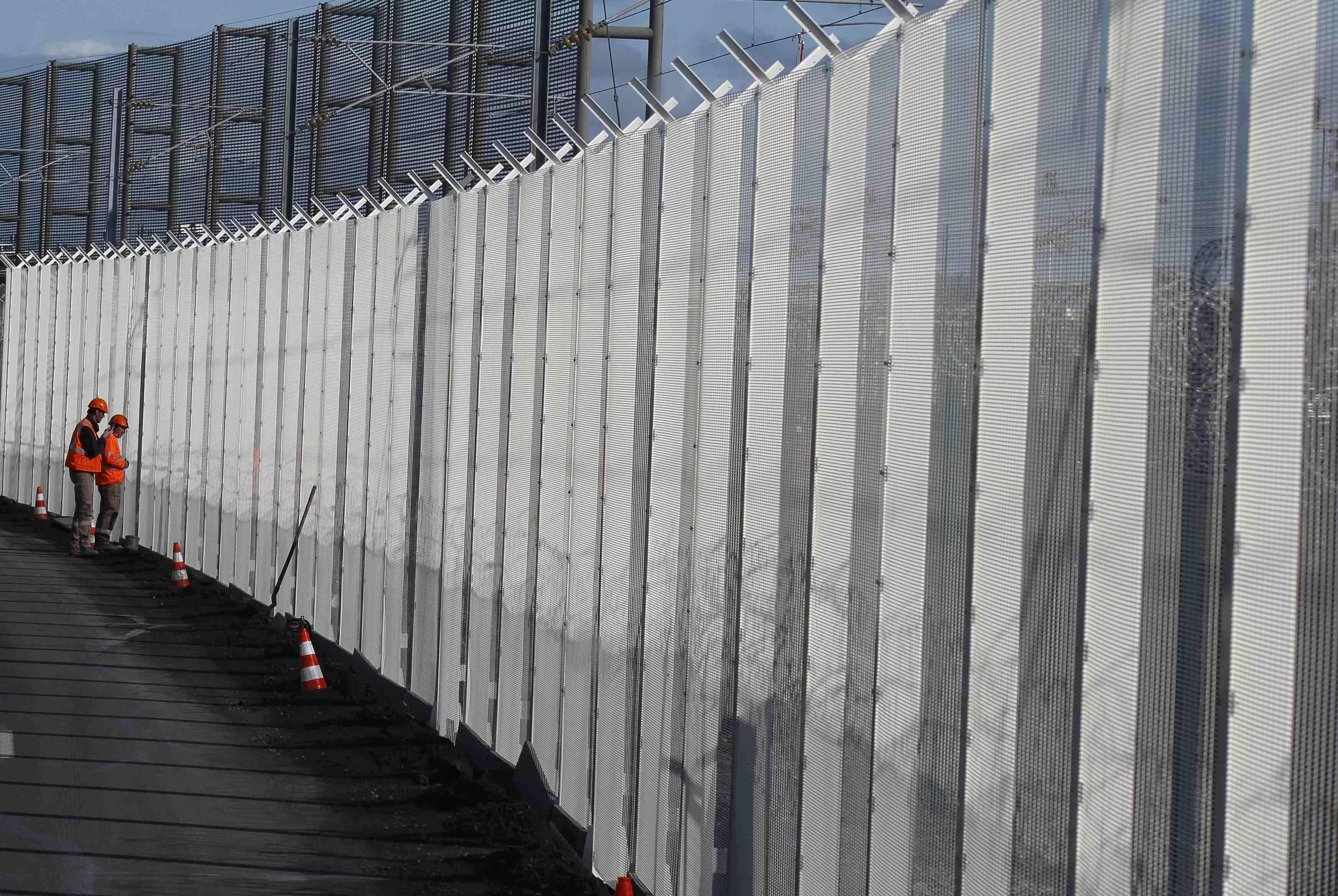 Para pekerja membangun pagar baru untuk menghentikan migran mengakses terminal Eurotunnel di Coquelles, dekat Calais, Prancis bagian utara, Selasa (20/10). Pengetatan keamanan di pelabuhan laut di Calais telah mendorong peningkatan upaya untuk mencapai Terowongan Channel, yang mengakibatkan kematian beberapa migran. ANTARA FOTO/REUTERS/Pascal Rossignol.