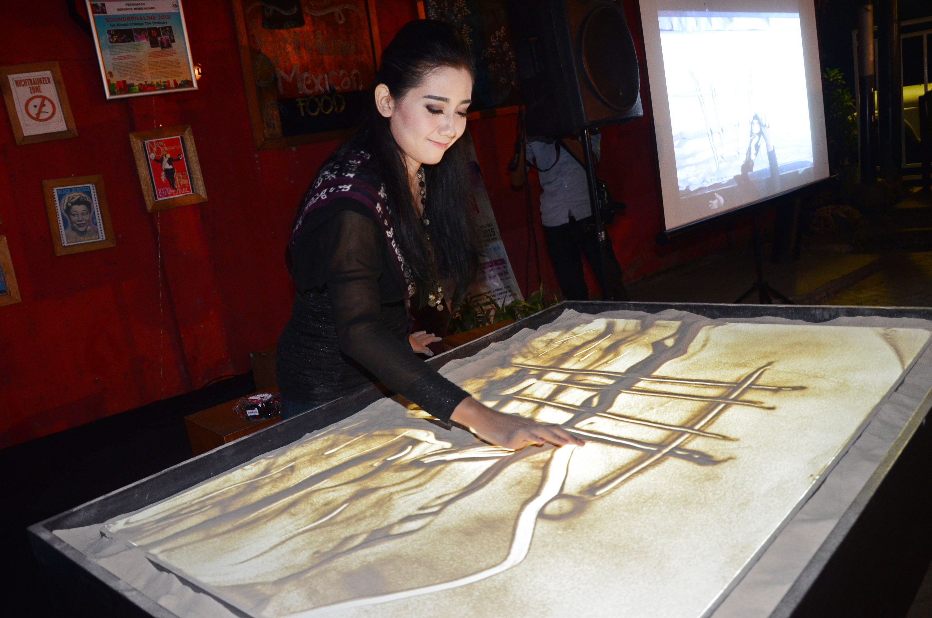 Baiq Amalia Putri Ghaesani (19) menunjukkan keahliannya melukis dengan media pasir saat menggelar pertunjukkan melukis pasir di Bandini Koffie, Mataram, NTB, Senin (26/10). Pertunjukkan melukis dengan media pasir yang berkolaborasi dengan pemusik Ary Juliant tersebut diselenggarakan sebagai penggalangan dana Baiq Amalia Putri Ghaesani untuk mengikuti pemilihan putri Pariwisata Indonesia 2015 mewakili NTB. ANTARA FOTO/Ahmad Subaidi.