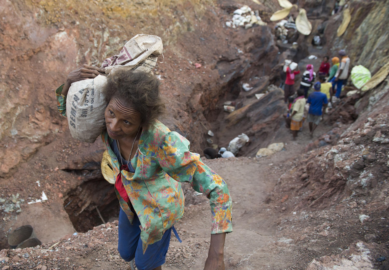 Penambang tradisional memanggul karung berisi mangan  di desa Oepuah, Moenleu, Timor Tengah Utara, NTT, Jumat (9/10). Para penambang tradisional tersebut dapat mengumpulkan 300-400 kilogram mangan per hari dengan harga per kilogram Rp700. ANTARA FOTO/Prasetyo Utomo.