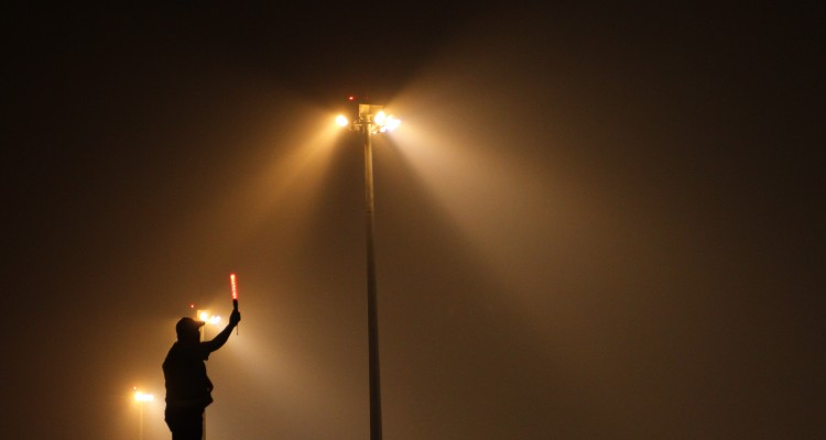 Seorang petugas memberi signal cahaya di tengah kabut asap saat bertugas di areal parkir pesawat Bandara Sultan Mahmud Baddarudin (SMB) II di Palembang, Sumsel, Senin (5/9). Kabut asap yang menyelimuti Bandara SMB II Palembang membuat jarak pandang di lintasan pesawat mengalami penurunan hingga 0,6 km. ANTARA FOTO/Nova Wahyudi.