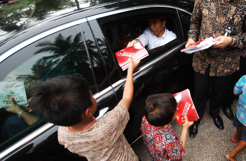 Presiden Joko Widodo membagi-bagikan buku tulis kepada anak-anak saat meninjau desa di Nagari Parik Malintang, Kab.Padangpariaman, Sumatera Barat, Kamis (8/10). Presiden mengunjungi sejumlah daerah di Sumatera Barat sebelum bertolak ke Riau dan Jambi untuk meninjau kawasan bencana kebakaran lahan yang mengakibatkan kabut asap. ANTARA FOTO/Iggoy el Fitra.