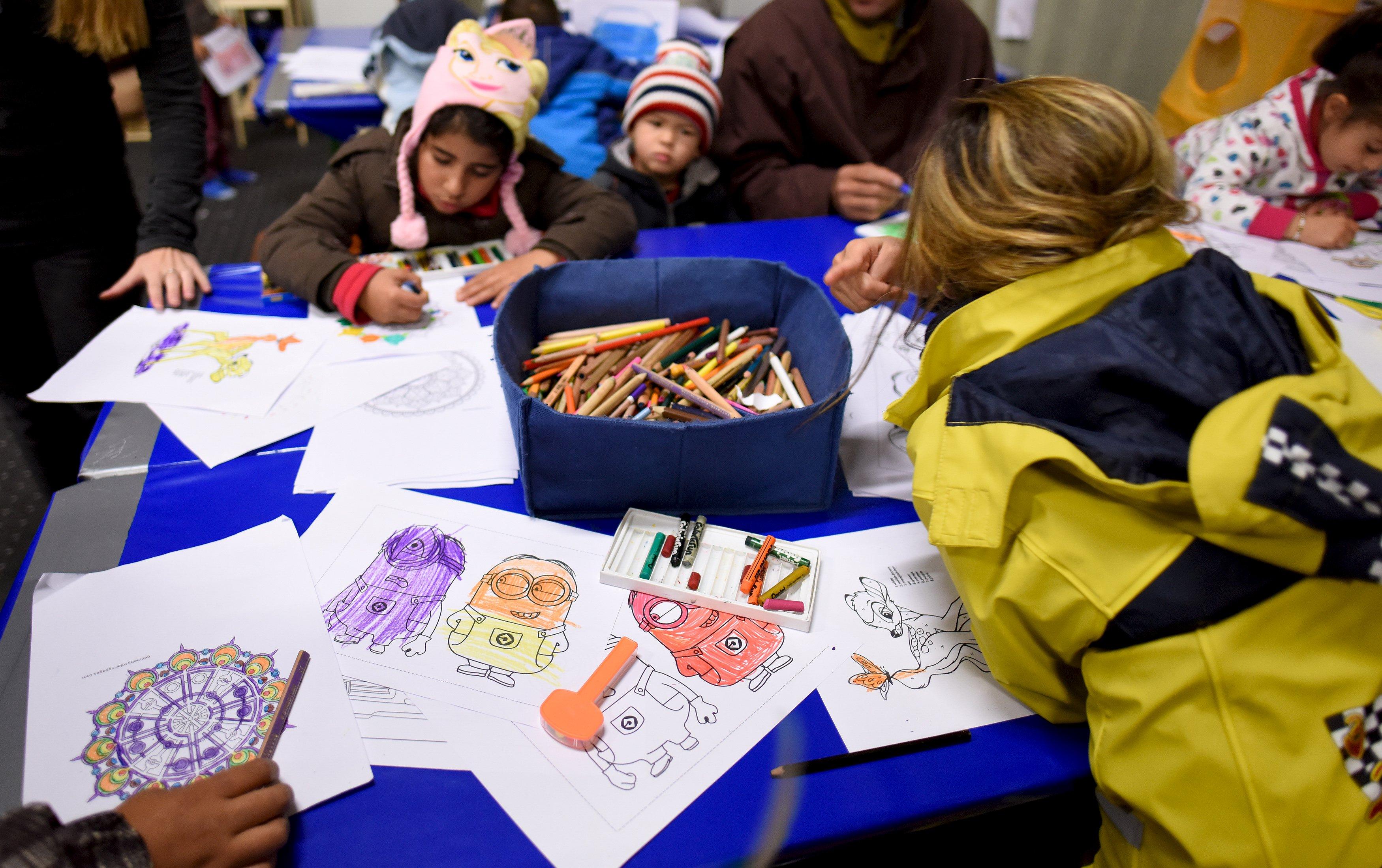 """Anak-anak migran mewarnai di ruang bermain di kamp pengungsi di Celle, Lower-Saxony, Jerman, 15 Oktober 2015. Dengan musim dingin yang akan segera datang, pihak berwenang berjuang untuk menemukan tempat yang hangat untuk ditempati oleh ribuan pengungsi yang datang ke Jerman setiap harinya. Dalam keputusasaan, mereka mencari ruang olahraga, hostel dan gedung kantor kosong. Tapi saat pilihan ini semakin sulit, tenda telah menjadi pilihan terbaik: terlepas dari suhu yang semakin menurun, sebuah survei oleh koran cetak Jerman """"Die Welt"""" menunjukkan setidaknya 42,000 pengungsi masih tinggal di tenda. Foto diambil tanggal 15 Oktober 2015. ANTARA FOTO/REUTERS/Fabian Bimmer."""