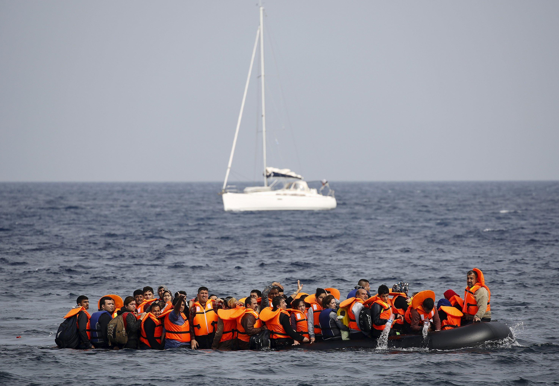 Pengungsi Suriah meminta pertolongan dan mengosongkan air dari perahu karet mereka yang tergenang saat mereka mendekati Pulau Lesbos Yunani, Selasa (20/10). Ribuan pengungsi - sebagian besar melarikan diri dari perang yang melanda Suriah, Afganistan dan Irak - setiap hari mencoba menyeberangi laut Aegean dari Turki, perjalanan singkat tapi berbahaya dalam perahu karet yang digunakan oleh migran, seringkali di laut yang berbahaya. Hampir 400,000 orang telah tiba di Yunani tahun ini, menurut UNHCR, melebihi kemampuan finansial sebuah negara untuk mengatasinya. ANTARA FOTO/REUTERS/Yannis Behrakis.