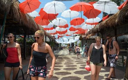 Sejumlah wisatawan melintas dibawah ribuan payung merah putih yang dipasang disepanjang jalan pantai Gili Trawangan, Desa Gili Indah, Tanjung, Lombok Utara, NTB, Rabu (30/9). Pemasangan payung sebanyak 2292 yang digagas Asosiasi Pengusaha Gili Trawangan dan Badan Promosi Pariwisata Daerah Lombok Utara tersebut memecahkan Rekor MURI Dunia pemasangan payung merah putih terbanyak tahun 2015. ANTARA FOTO/Ahmad Subaidi.