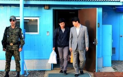 Joo Won-moon (tengah), yang pernah menjadi mahasiswa Universitas New York, tiba di desa gencatan senjata Panmunjom di zona demiliterisasi (DMZ) memisahkan dua Korea, Korea Selatan, dalam foto handout yang diberikan oleh Kementerian Penyatuan dan disiarkan Yonhap, Senin (5/10). Korea Utara memulangkan mahasiswa Korea Selatan yang memiliki kartu hijau Amerika Serikat kemarin, enam bulan setelah menangkapnya saat menyeberang melalui Tiongkok, menurut keterangan Kementerian Penyatuan Korea Selatan. ANTARA FOTO/REUTERS/the Unification Ministry/Yonhap.