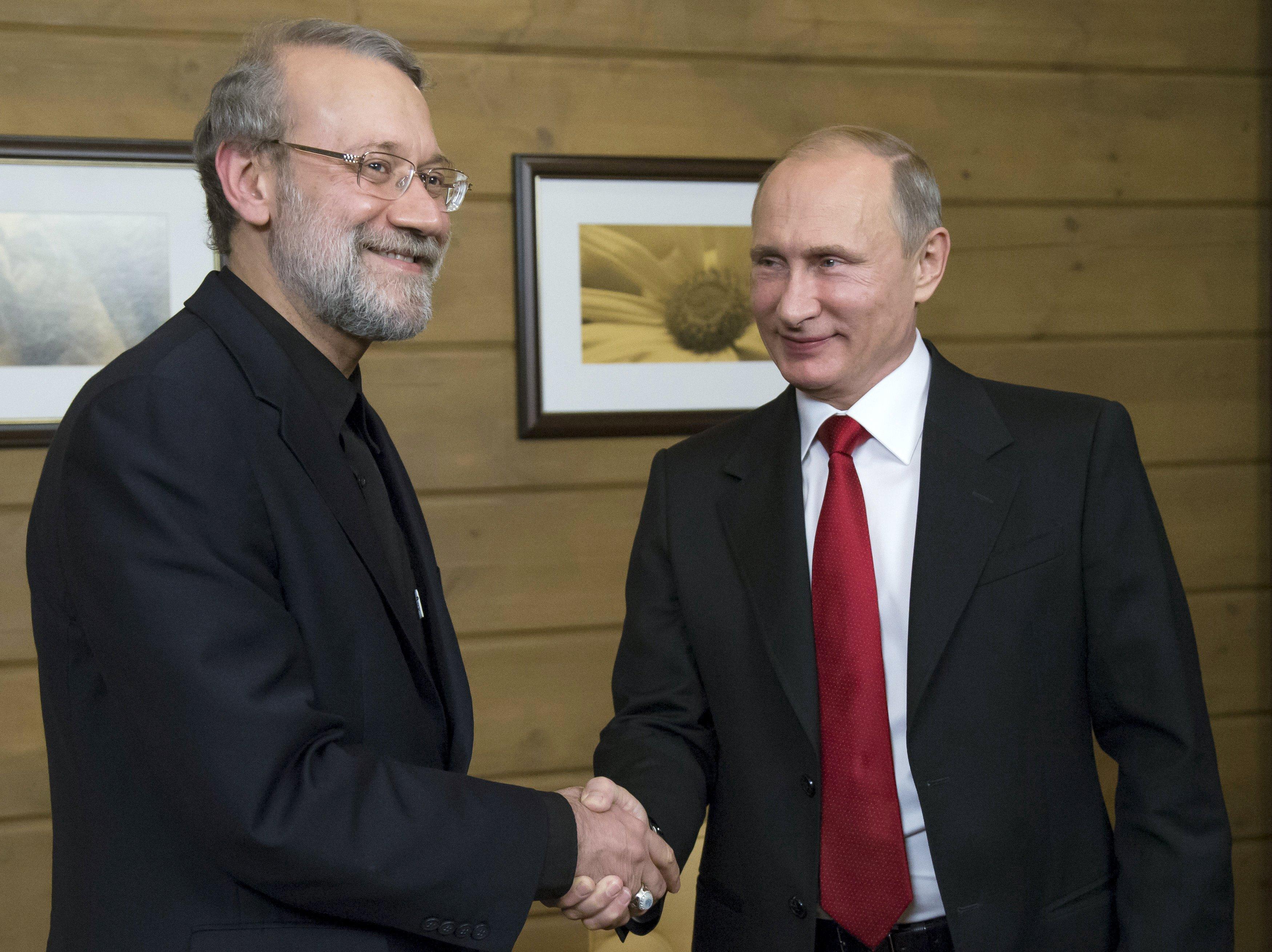 Presiden Rusia Vladimir Putin (kanan) bersalaman dengan Ketua Parlemen Iran Ali Larijani saat mereka bertemu setelah sesi Klub Diskusi Internasional Valdai di Sochi, Rusia, Kamis (22/10). ANTARA FOTO/REUTERS/Alexander Zemlianichenko.
