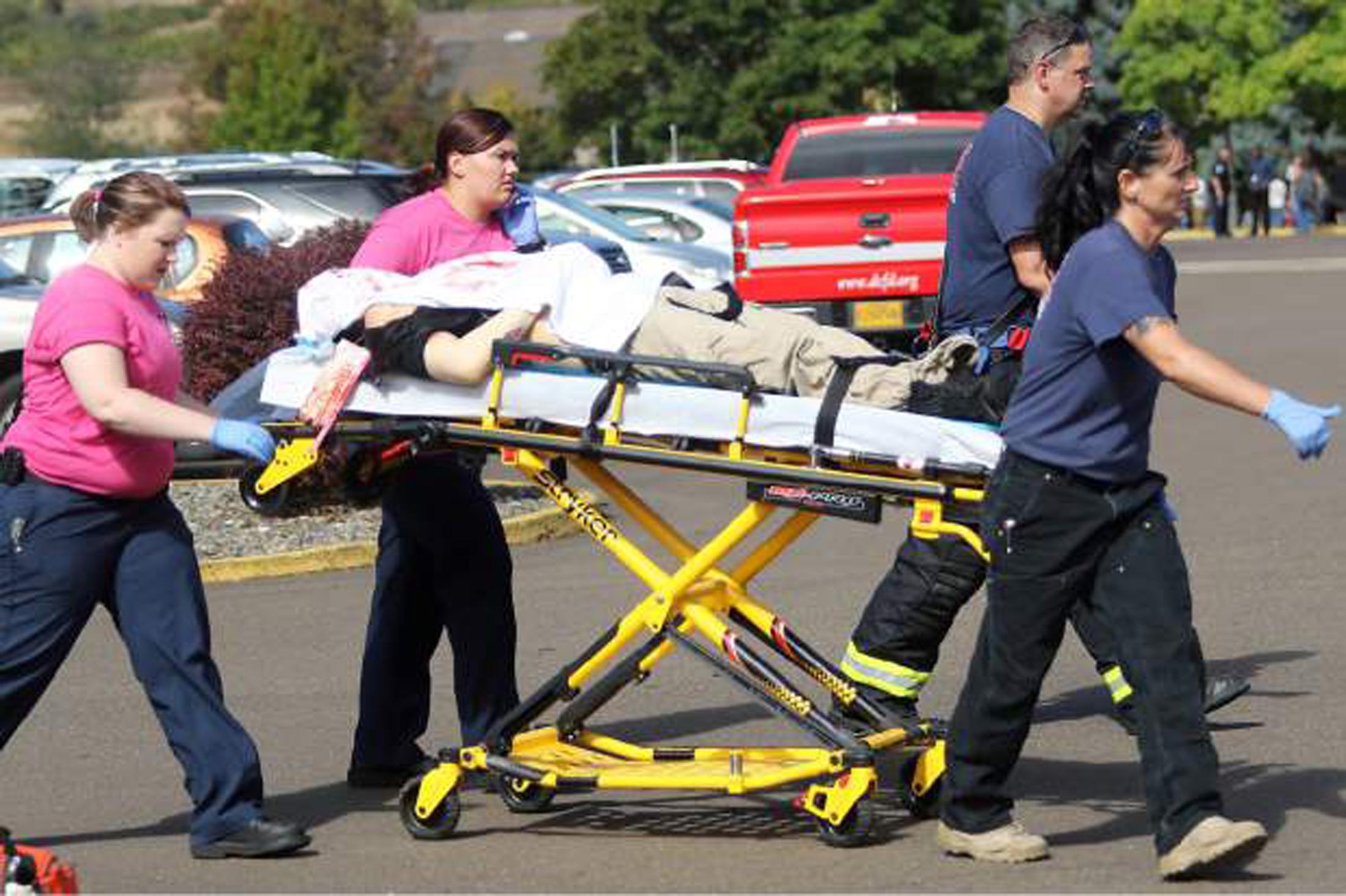 Petugas gawat darurat memindahkan seseorang yang terluka setelah adanya insiden penembakan di Kampus Umpqua di Roseburg, Oregon, Kamis (1/10). Pria bersenjata melepaskan tembakan di sebuah komunitas kampus di Oregon, menewaskan 13 orang dan melukai 20 lainnya sebelum akhirnya ditembak mati oleh aparat hukum, dalam pembunuhan masal terbaru yang mengguncang sekolah Amerika Serikat, menurut keterangan jaksa wilayah dan sheriff setempat. ANTARA FOTO/REUTERS/Michael Sullivan/The News-Review.
