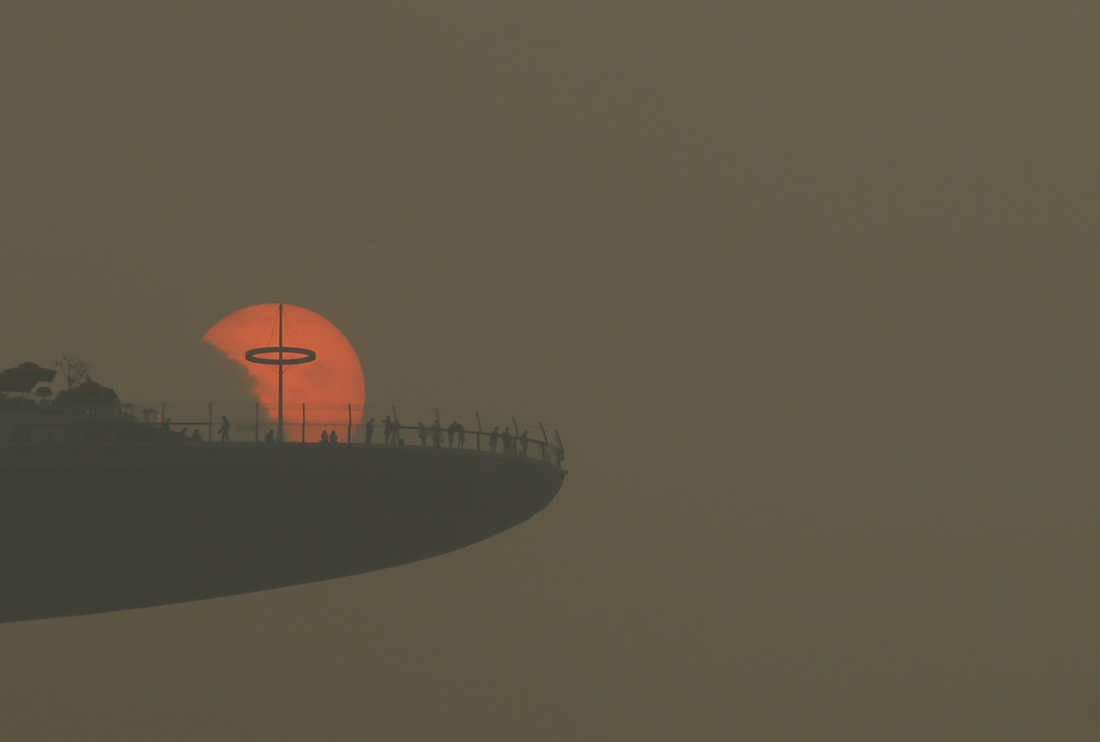 Warga memperhatikan matahari tenggelam dari dek observasi hotel Marina Bay Sands di Singapura, Senin (5/10). Indeks Standar Polutan (PSI) tiga-jam mencapai angka 186 pada jam 4 sore kemarin, menurut Lembaga Lingkungan Nasional. Penebangan dan pembakaran hutan untuk perkebunan di wilayah Indonesia telah menyelimuti Singapura dengan asap menyesakkan selama beberapa pekan. ANTARA FOTO/REUTERS/Edgar Su.