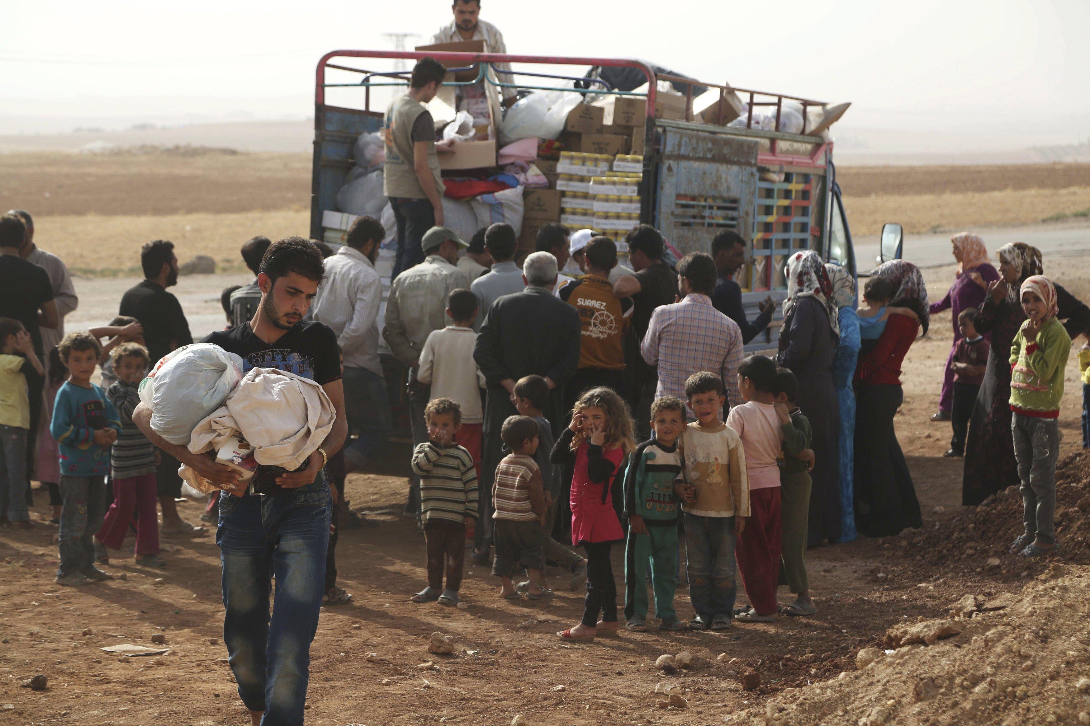 Penduduk Suriah yang melarikan diri dari peperangan di wilayah mereka menerima bantuan kemanusiaan di pinggiran desa Aleppo bagian selatan, Suriah, Rabu (21/10). Perang di Suriah telah membuat sebanyak 35,000 orang mengungsi dari Hader dan Zerbeh di pinggiran barat daya kota Aleppo beberapa hari yang lalu, kata pihak PBB untuk Koordinasi Kemanusiaan (OCHA) pada hari Senin. ANTARA FOTO/REUTERS/Hosam Katan.