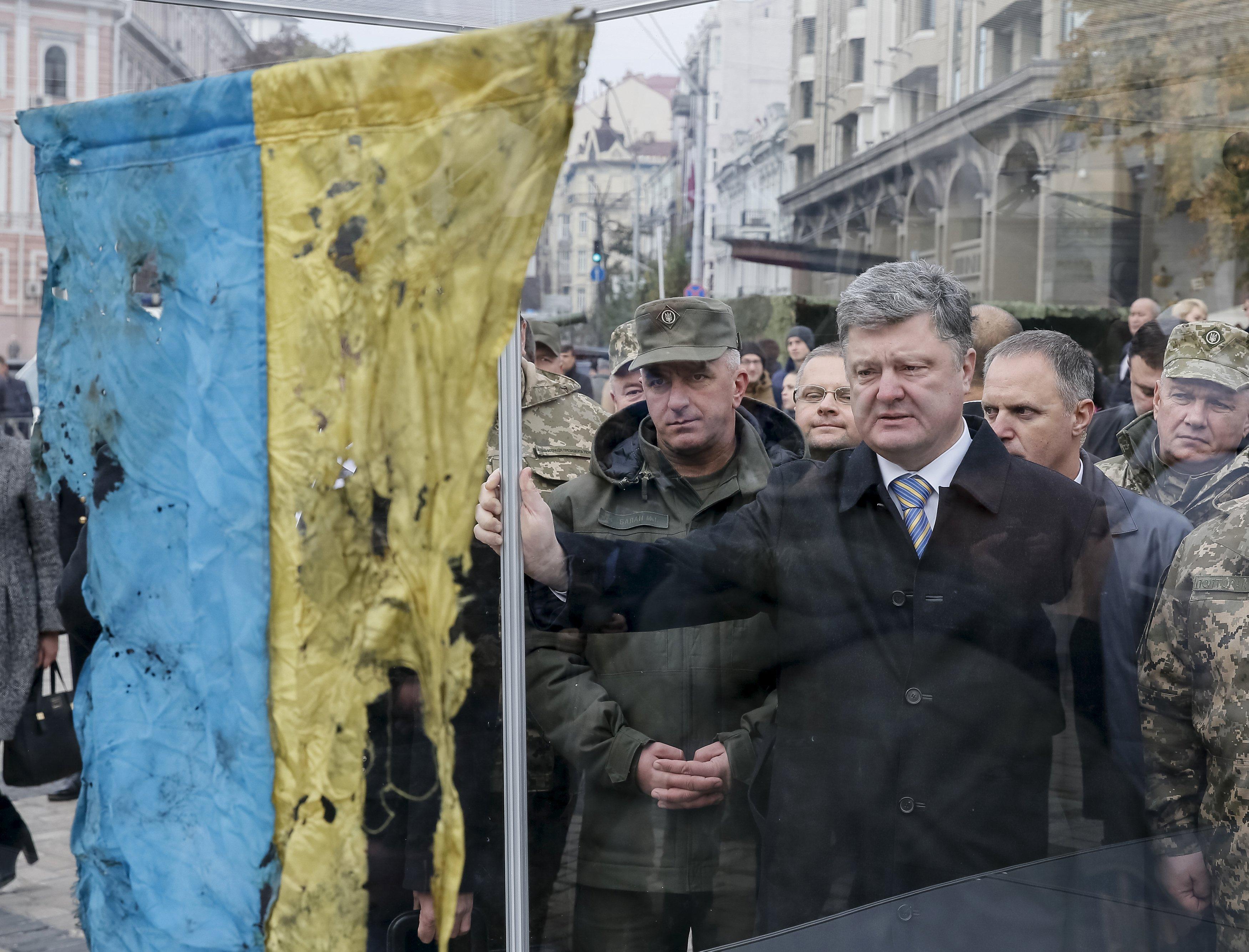 Presiden Ukraina Petro Poroshenko (tengah) melihat bendera Ukraina yang dibawa dari wilayah timur Ukraina dimana konflik militer terjadi, selama kunjungannya di pameran peralatan militer baru di Kiev, Ukraina, 14 Oktober 2015. Ukraina merayakan Hari Pertahanan pada hari Rabu. ANTARA FOTO/REUTERS/Gleb Garanich.