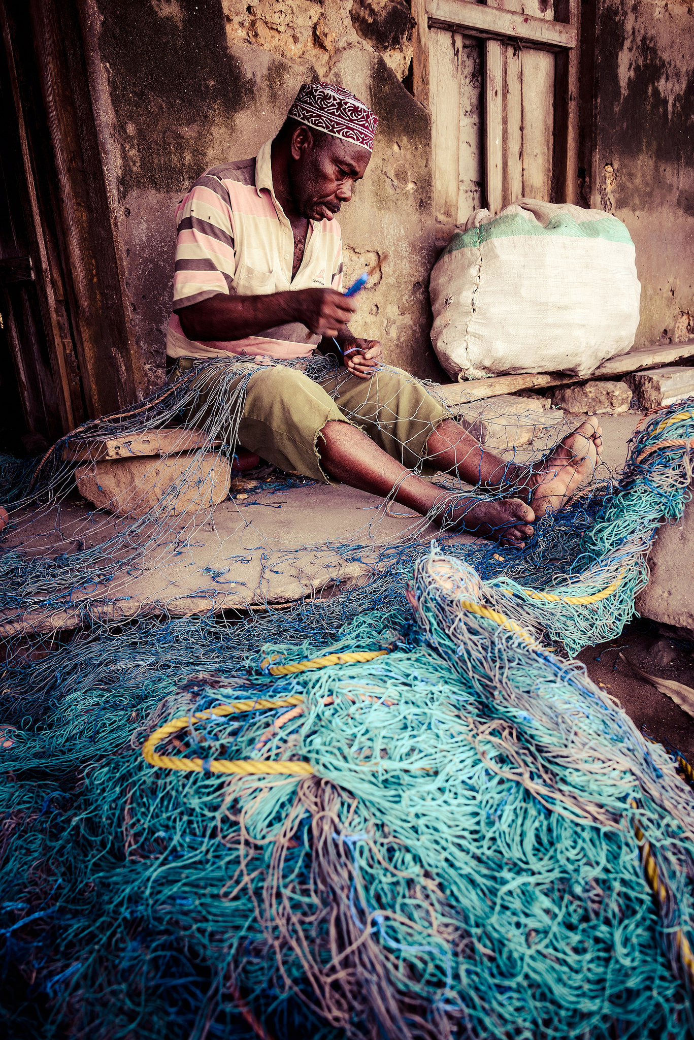 Mending nets and preparing for the next night in the fishing harbour of Stonetown, Zanzibar. Flickr - Christiane Birr.