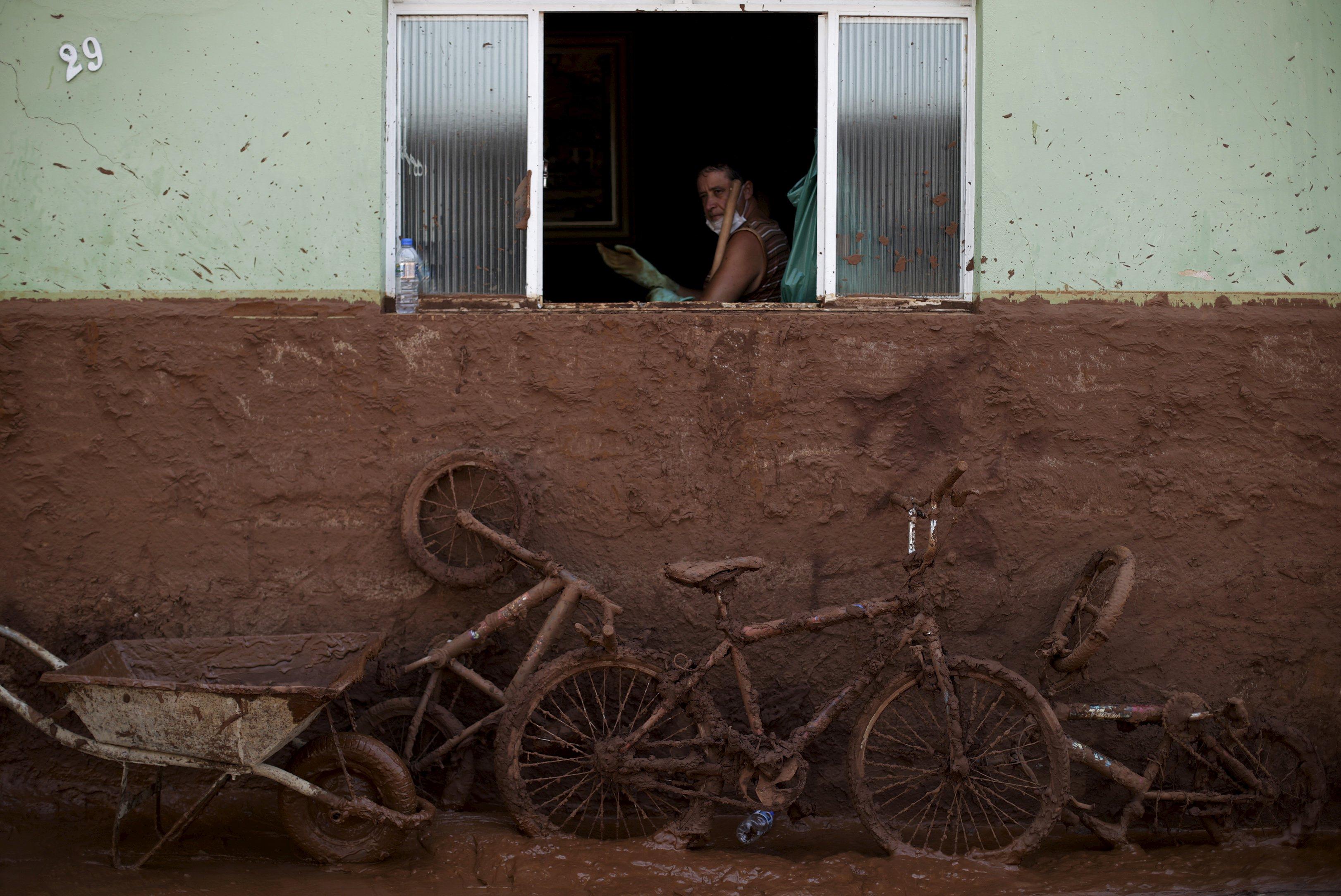 Seorang pria membersihkan rumah yang dibanjiri lumpur setelah bendungan yang dimiliki oleh Vale SA dan BHP Biliton Ltd hancur, di Barra Longa, Brazil, Sabtu (7/11). Jumlah korban dari dua bendungan di tambang Brazil akan meningkat di hari mendatang, menurut walikota pada hari Sabtu, saat 10 warga dari desa terdekat masih hilang selain 13 penambang. Hingga saat ini satu pekerja dikonfirmasi tewas dalam bencana yang dideskripsikan oleh gubernur Minas Gerais sebagai bencana lingkungan terparah di negeri itu. REUTERS/Ricardo Moraes.