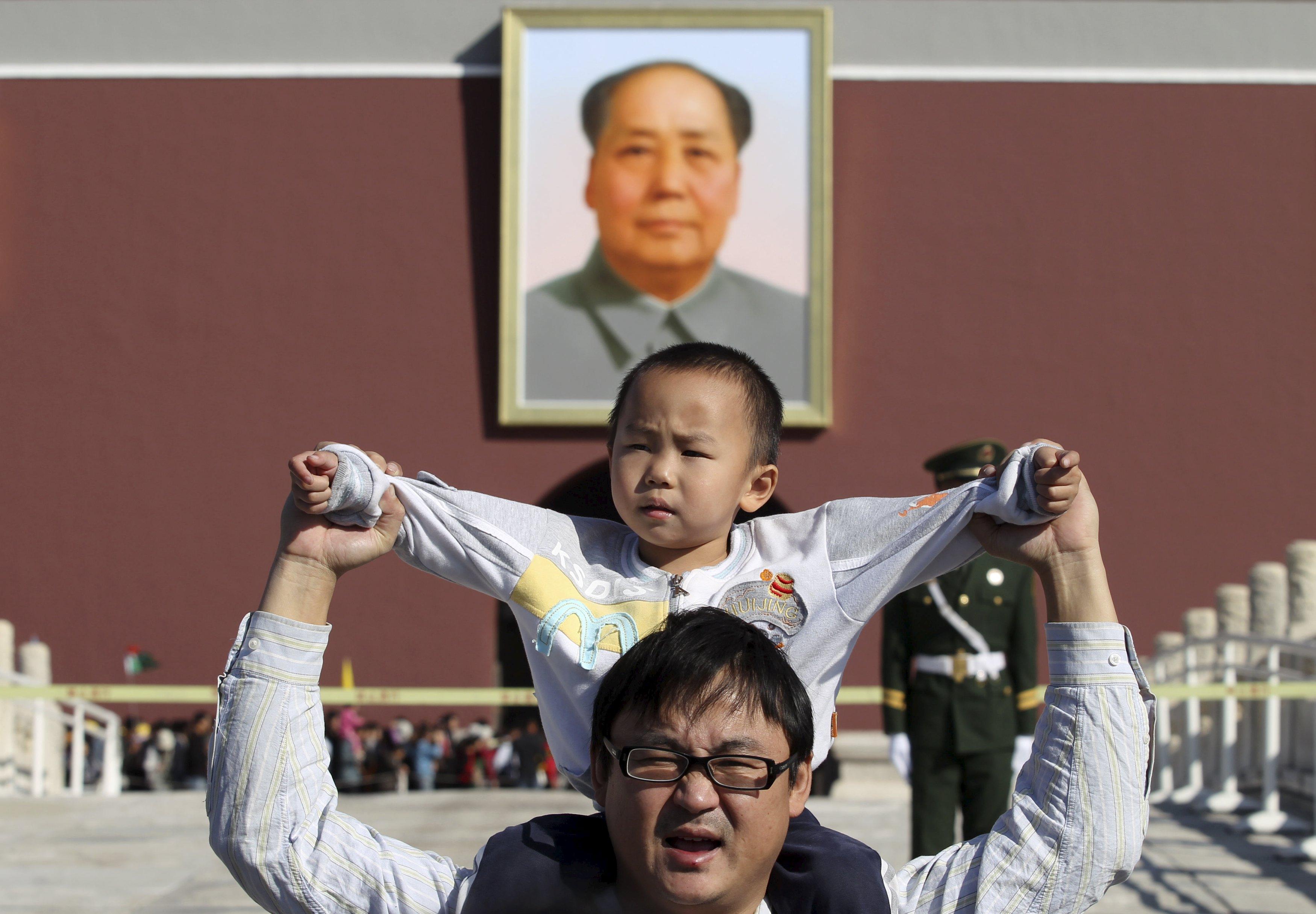 Anak laki-laki duduk di bahu ayahnya saat berpose di depan foto raksasa Mao Zedong di lapangan Tiananmen, Beijing, Tiongkok, 2 Oktober 2011. Tiongkok mengurangi pembatasan keluarga berencana dengan memperbolehkan keluarga memiliki dua anak setelah puluhan tahun menerapkan kebijakan satu anak dengan ketat, menurut Partai Komunis berkuasa pada hari Kamis (29/10), langkah yang ditujukan untuk menambah angka penduduk dalam perkembangan ekonomi. Foto diambil pada tanggal 2 Oktober 2011. REUTERS/Stringer.