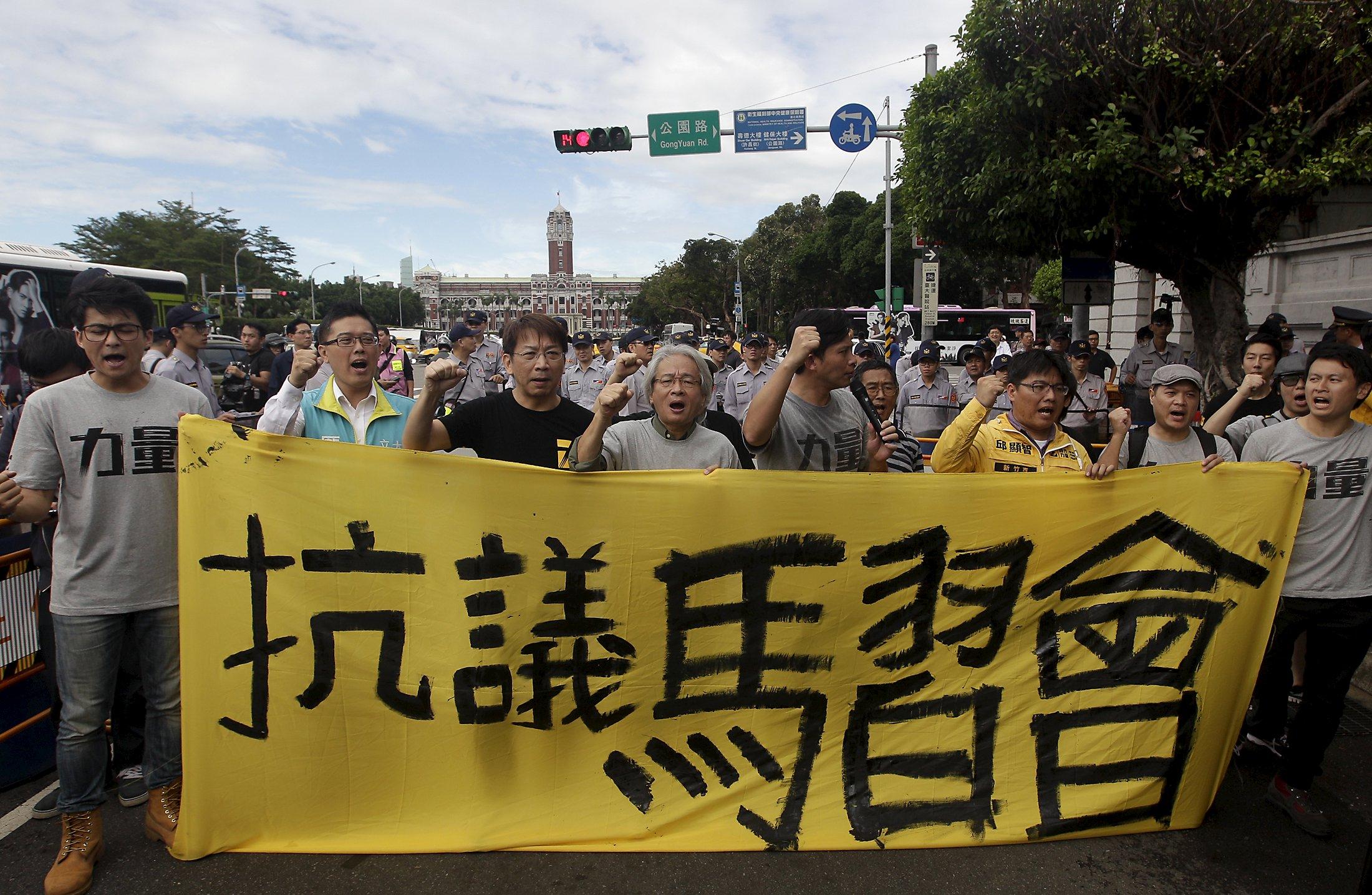 """Para aktivis meneriakkan slogan saat memrotes pertemuan antara Presiden Taiwan Ma Ying-jeou dan Presiden Tiongkok Xi Jinping sementara polisi berjaga di depan Istana Kepresidenan di Taipei, Taiwan, Rabu (4/11). Presiden Tiongkok Xi Jinping akan mengadakan pembicaraan dengan Presiden Taiwan Ma Ying-jeou di Singapura hari Sabtu dalam pertemuan pertama kedua pemimpin tersebut sejak perang sipil Tiongkok berakhir tahun 1949. Spanduk bertuliskan """"Protes pertemuan antara Ma dan Xi"""". REUTERS/Pichi Chuang."""