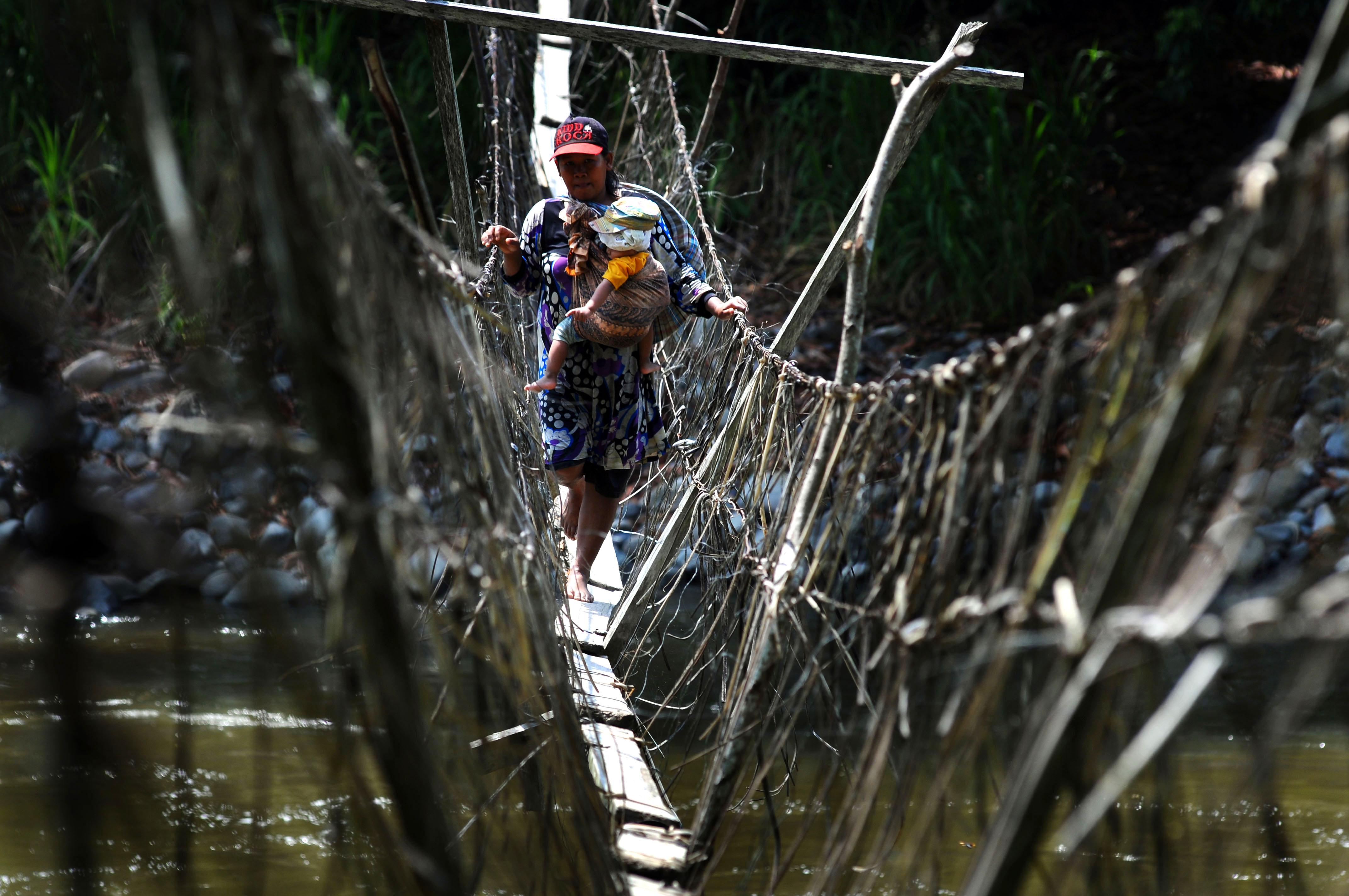 Seorang ibu sambil menggendong anaknya meniti jembatan darurat  di Desa Makujawa, Gimpu, Sigi, Sulawesi Tengah, Sabtu (7/11). Jembatan darurat yang panjangnya kurang lebih 300 meter itu satu-satunya akses untuk menuju dusun satu Wahi dan perkebunan masyarakat. ANTARA FOTO/Fiqman Sunandar.