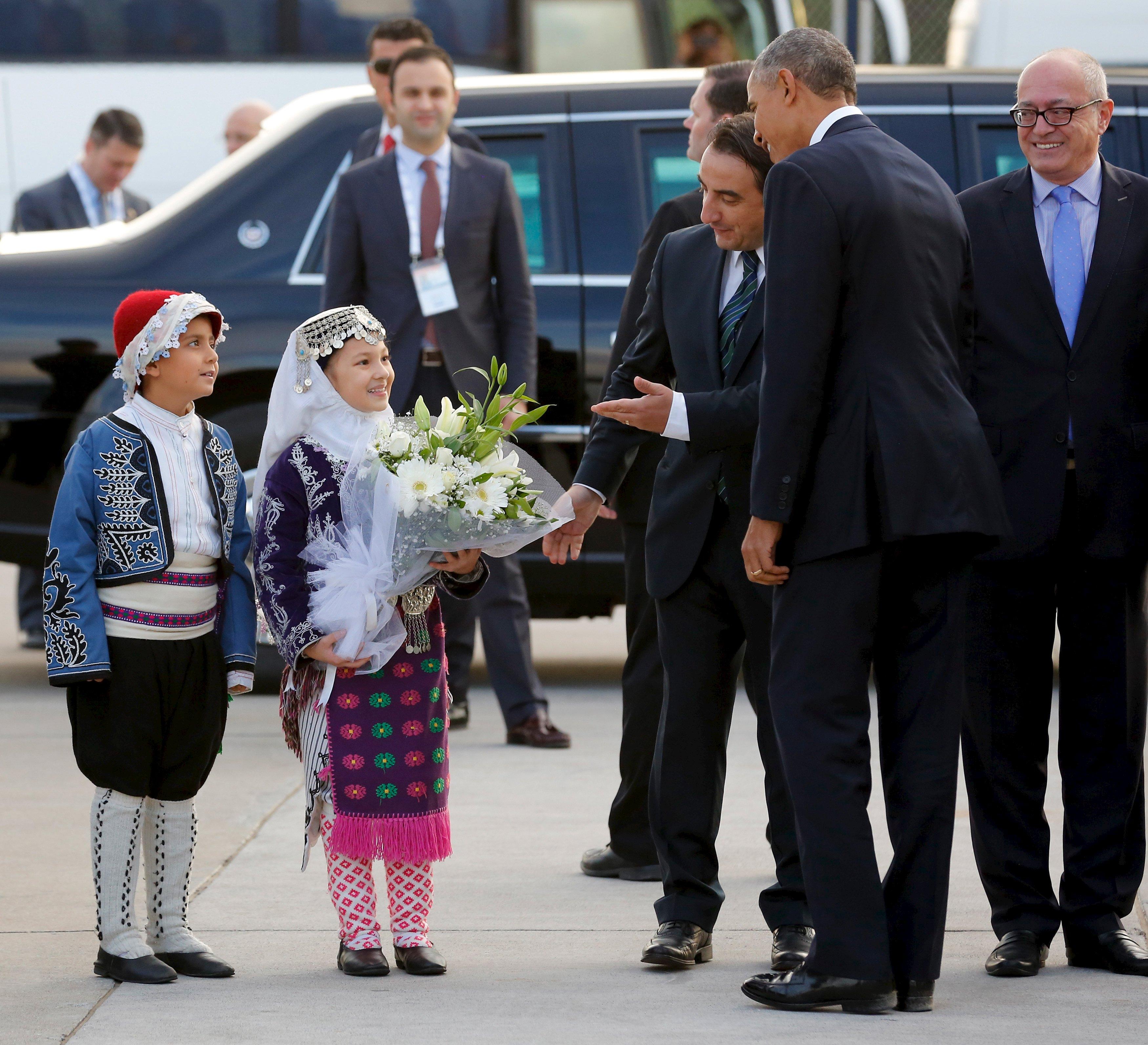 Dua anak memberikan rangkaian bunga kepada Presiden Amerika Serikat Barack Obama saat tiba di Bandara Internasional Antalya, Turki, Minggu (15/11). ANTARA FOTO/REUTERS/Jonathan Ernst.