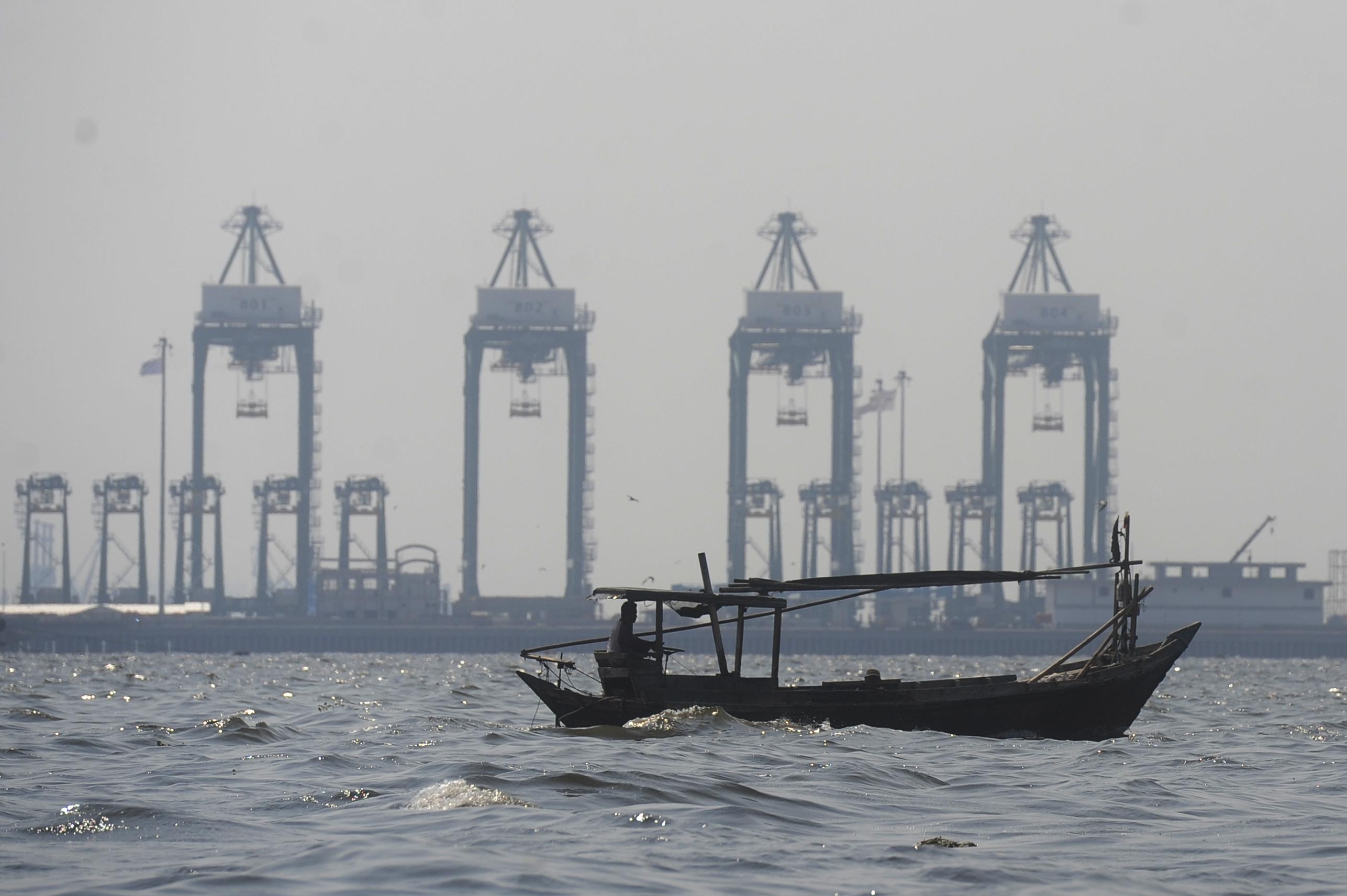 Nelayan melintas dengan latar belakang pelabuhan peti kemas Tanjung Priok di perairan Teluk Jakarta, Kamis (5/11). Menurut Otoritas Jasa Keuangan (OJK), penyaluran kredit baru perikanan dan kelautan melalui delapan bank nasional mencapai Rp4,41 triliun atau 82,09 persen dari target sebesar Rp5,37 triliun. ANTARA FOTO/Wahyu Putro A.