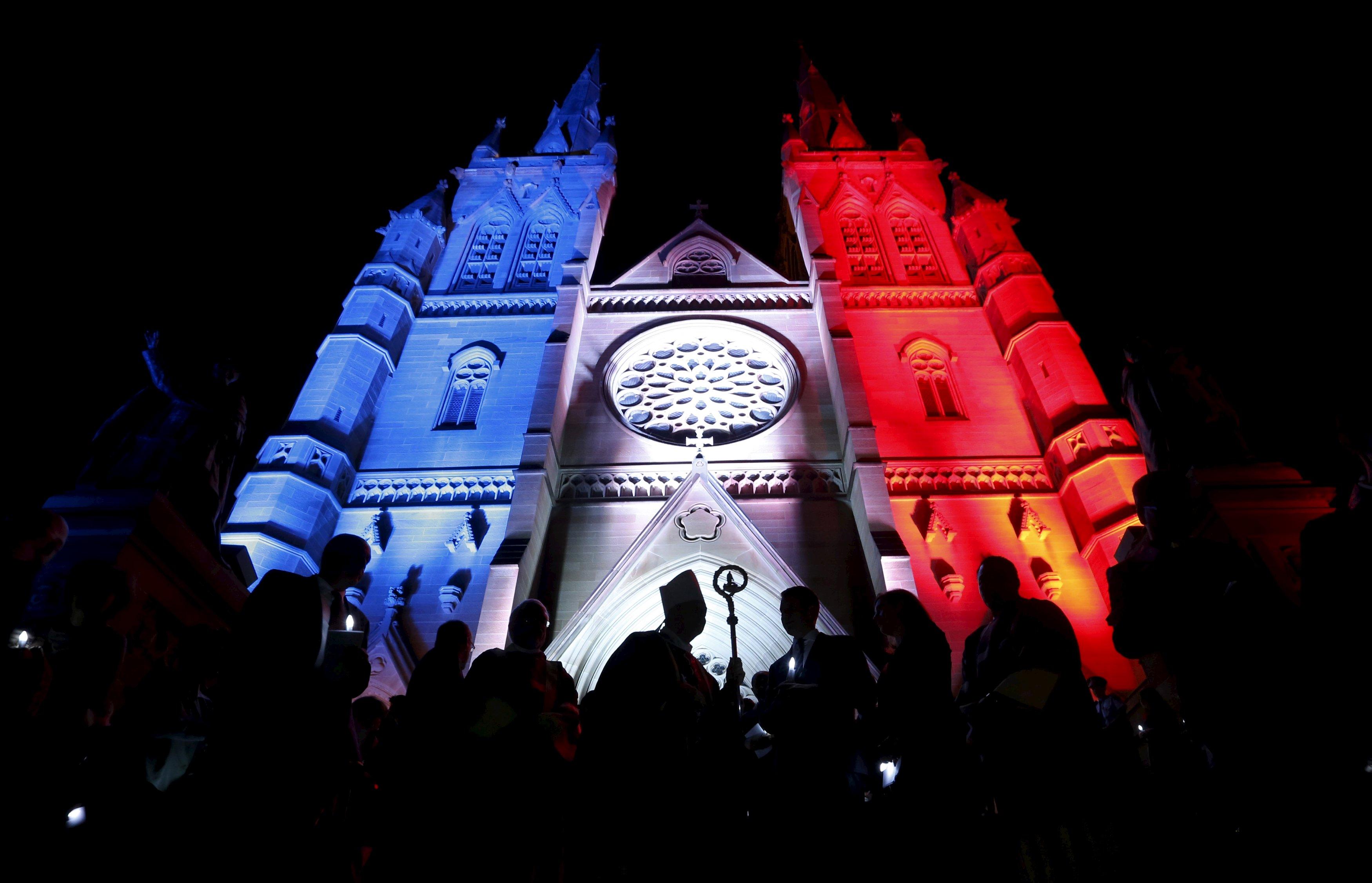 Warga mengikuti Misa Requiem bagi korban serangan Paris di depan Katedral St. Mary yang dihiasi warna bendera Perancis, biru, putih dan merah di Sydney, Australia, Senin (16/11). ANTARA FOTO/REUTERS/Jason Reed.