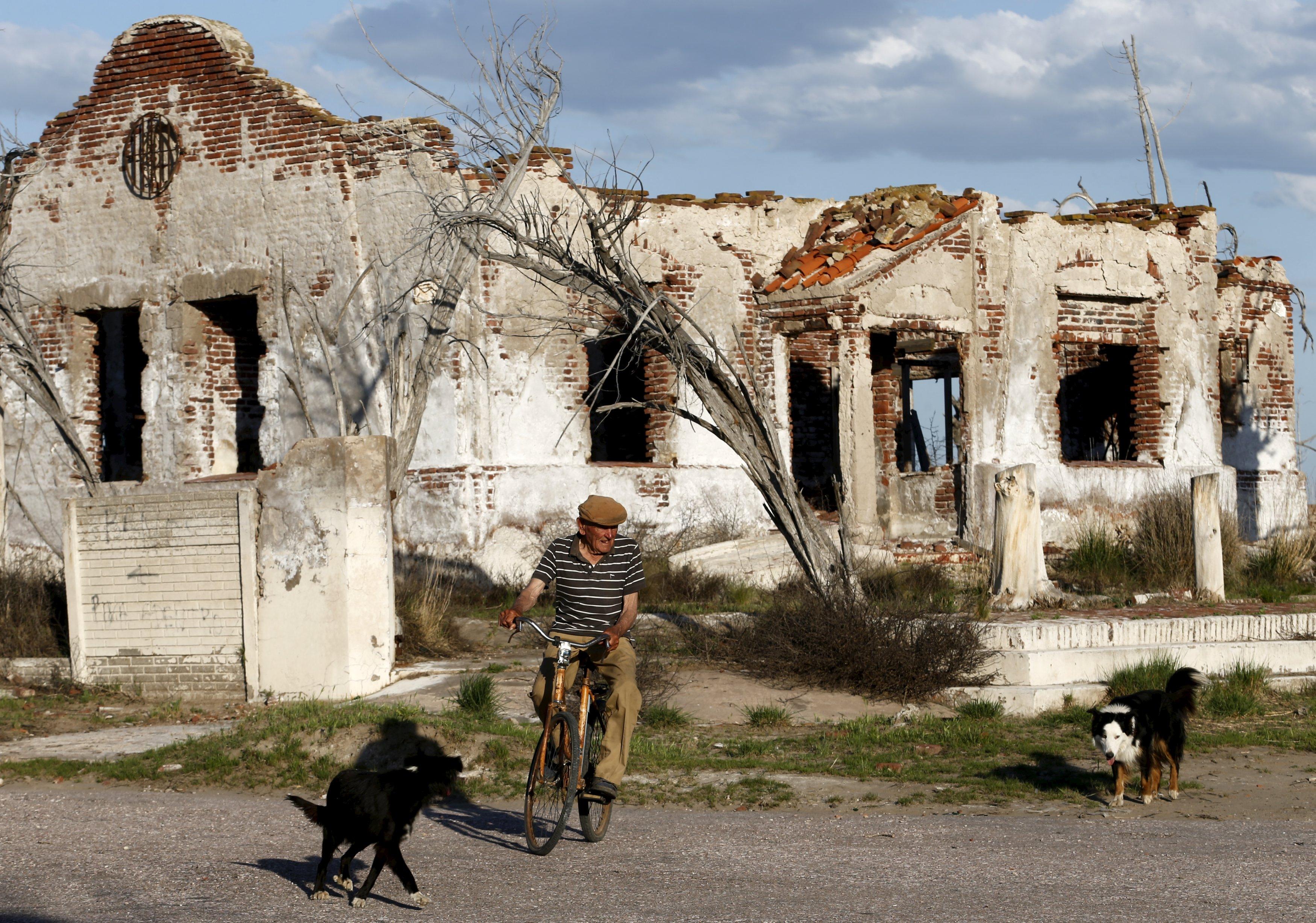 Pablo Novak, 85 tahun, mengendarai sepedanya melewati reruntuhan rumah di Desa Epecuen, Jumat (6/11). Selama beberapa tahun terakhir kota Epecuen, yang berlokasi di 550 km barat daya Buenos Aires, menarik perhatian turis dengan suasana apokaliptik menakutkan setelah banjir merendam kota tersebut dengan air asin selama lebih dari dua dekade. Semula desa turis samping danau yang sibuk di tahun 1920-an dikenal untuk pemandian air garamnya, Epecuen tiba-tiba berakhir tanggal 10 November 1985 ketika hujan turun saat musim dingin menyebabkan Lago Epecuen meluap dan air pasang melewati dinding spesial khusus memasuki kota. Warga dan turis dipaksa evakuasi dan dalam beberapa hari rumah-rumah dan gedung-gedung tergenang air asin setinggi hampir 10 meter. Sekarang, 30 tahun kemudian, air telah menguap dan warga yang dulu tinggal disana bisa berjalan di reruntuhan berkarat kota tersebut. Foto diambil tanggal 6 November 2015. REUTERS/Enrique Marcarian.
