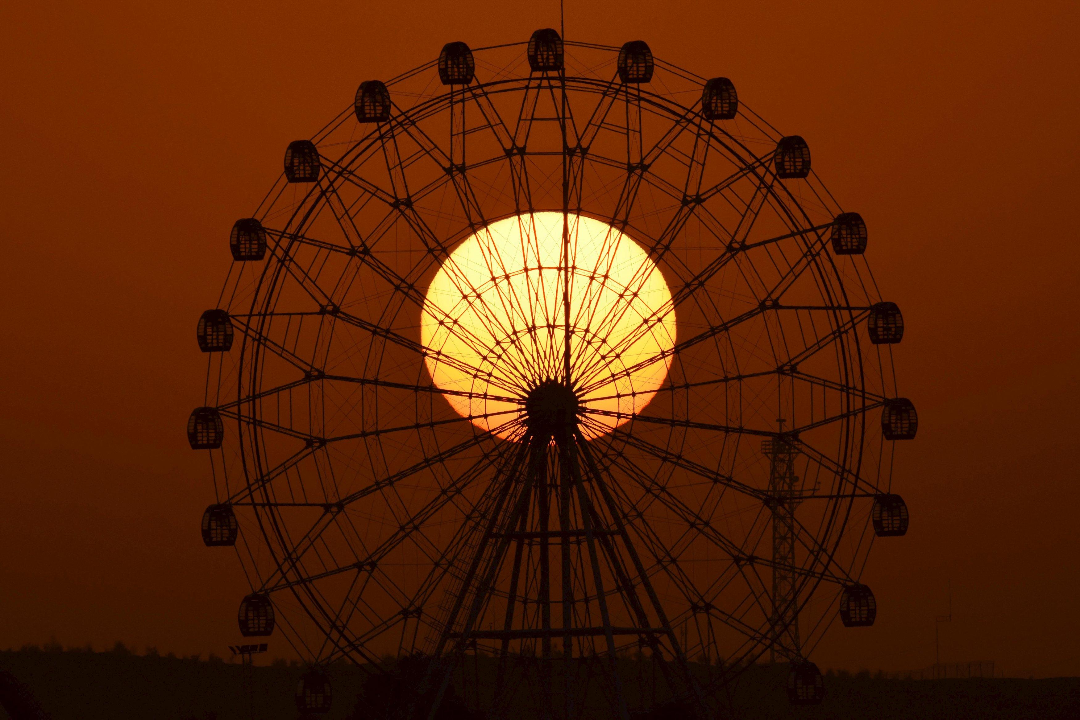 Matahari terbit terlihat di belakang bianglala di Korla, Wilayah Otonomi Xinjiang Uighur, Selasa (10/11). REUTERS/China Daily.