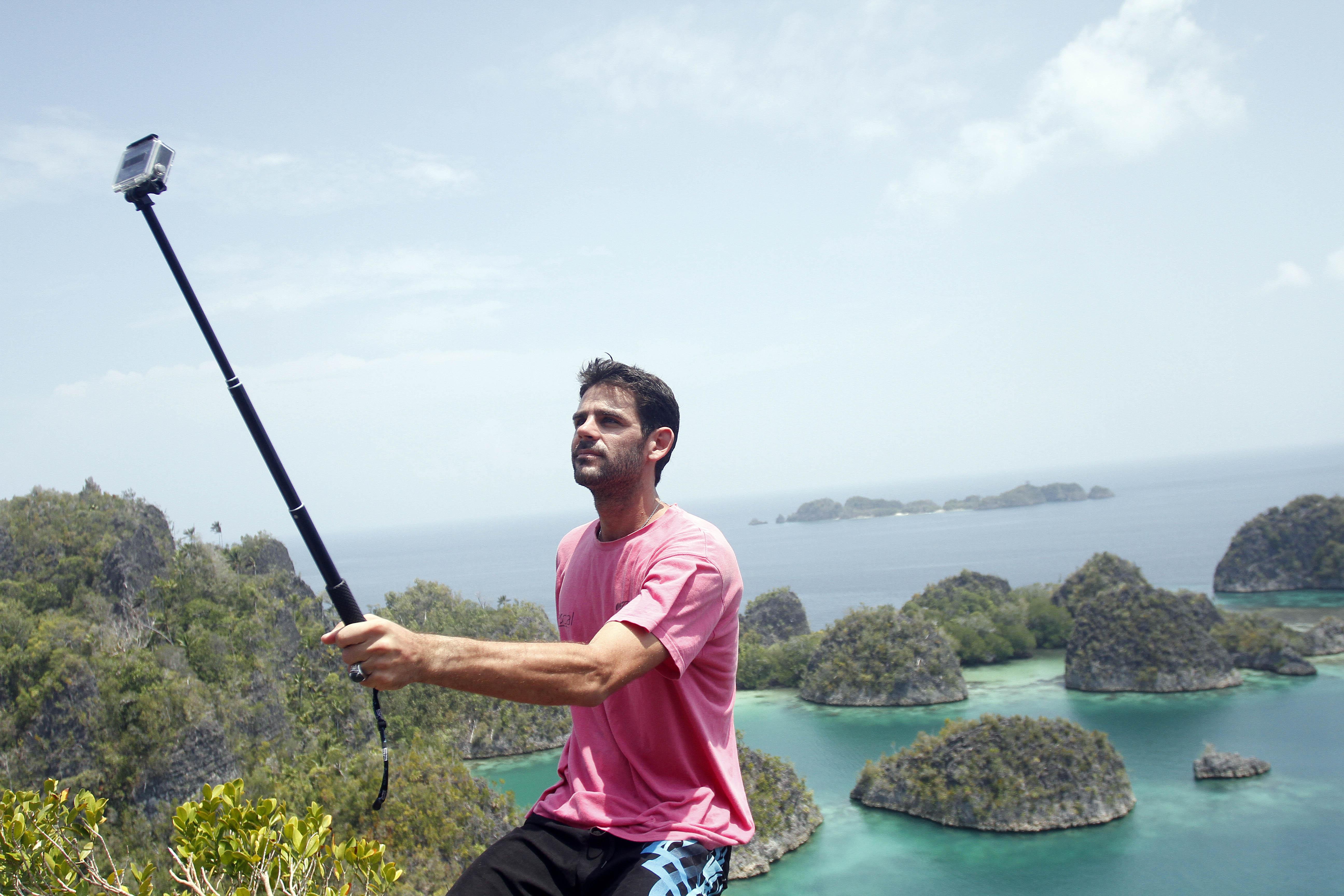 Seorang wisatawan mancanegara berfoto diri dengan latar belakang pemandangan di Pianemo, Raja Ampat, Papua Barat, Senin (2/11). Untuk menempuh jalan menuju lokasi tersebut dari Waigeo di Waisai (Ibu Kota Kabupaten Raja Ampat) adalah dua jam perjalanan, dengan menyewa 'speed boat' seharga Rp 5 juta sehari. ANTARA FOTO/Regina Safri.