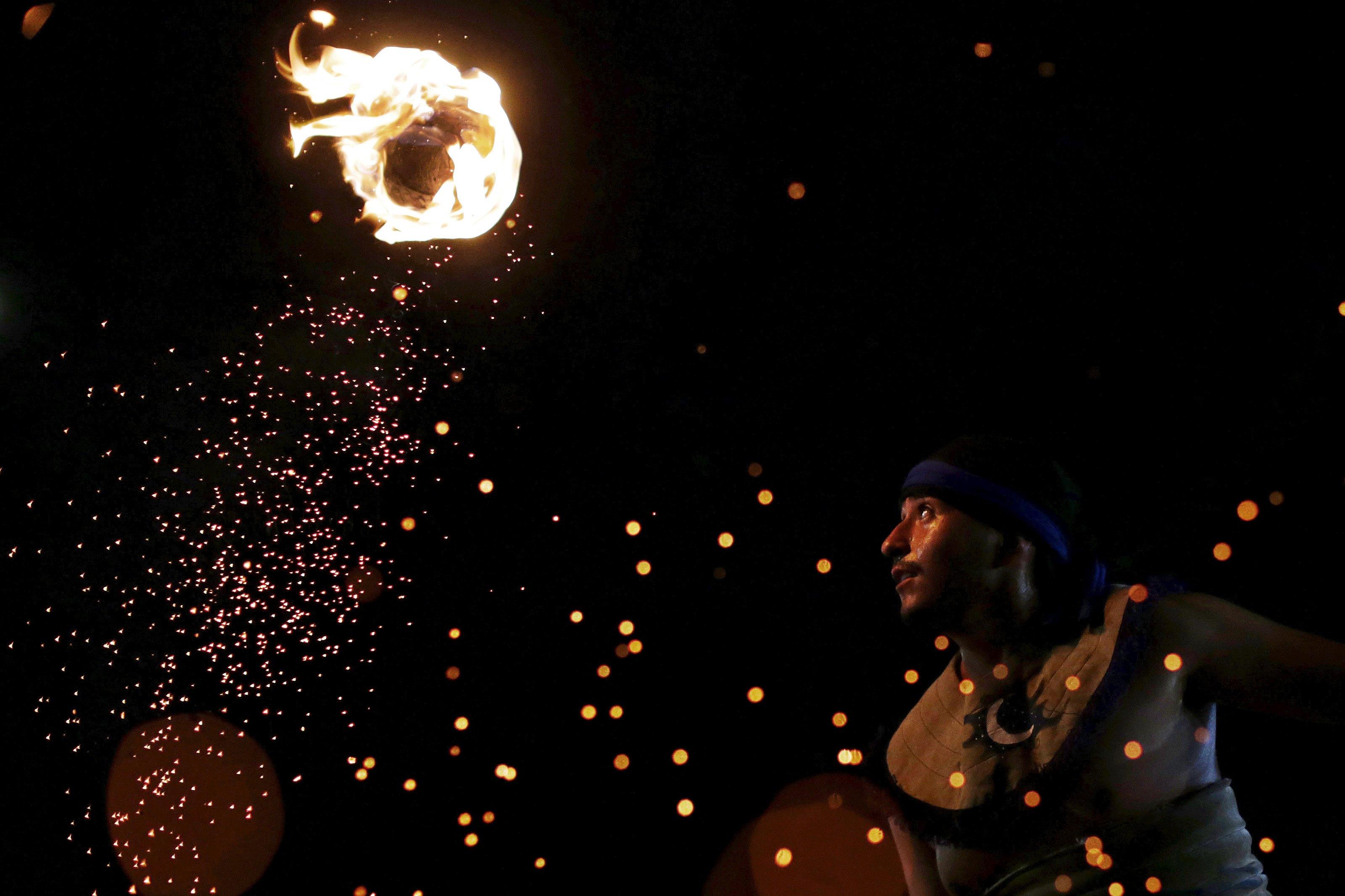 """Seorang pria pribumi dari Meksiko menunjukkan permainan Meksiko yang dikenal sebagai """"La Batalla"""" (permainan menggunakan bola api) saat World Games untuk Penduduk Pribumi di Palmas, Brazil, Kamis (29/10). REUTERS/Ueslei Marcelino."""