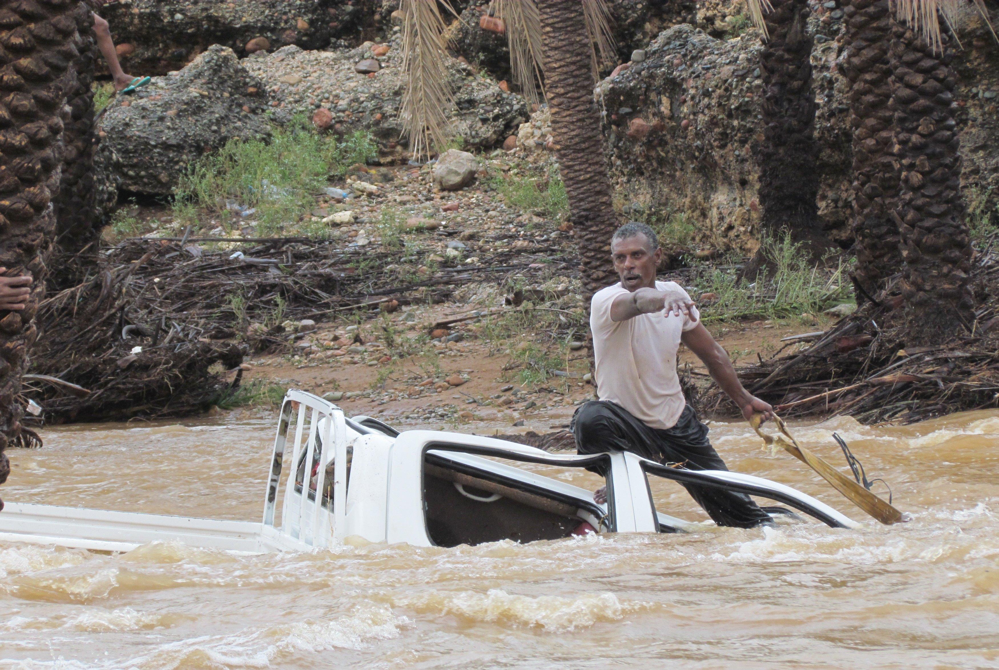 Seorang pria naik ke atap mobil saat mencoba menarik kendaraan yang terseret arus banjir di pulau Socotra Yaman, Senin (2/11). Siklon tropis langka yang menyebabkan badai angin yang menewaskan tiga orang dan melukai puluhan lainnya di pulau Socotra Yaman pada hari Senin, menurut warga dan pejabat. REUTERS.