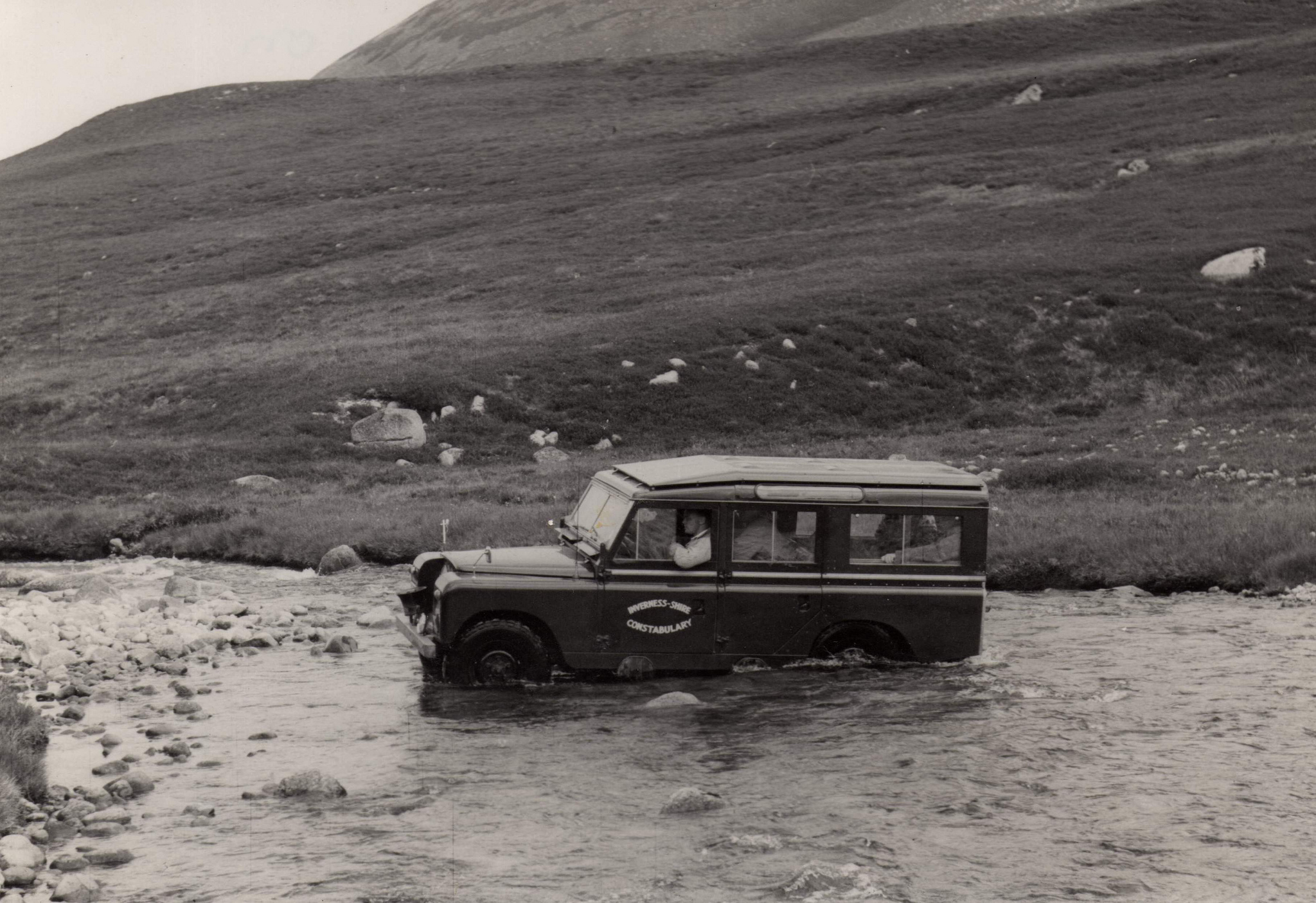 """Green LWB Land Rover of Inverness-shire Constabulary demonstrates """"off road"""" rather well as it negotiates a river high in the Cairmgorms range during Mountain Rescue duty. Flickr - Dave Conner."""