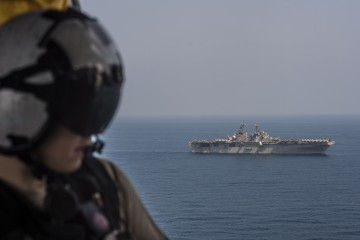 "USS Essex is underway in the Gulf of Aden. GULF OF ADEN (Oct. 26, 2015) Naval Air Crewman 3rd Class Justen Thurman communicates with pilots from the ""Blackjacks"" of Helicopter Sea Combat Squadron (HSC) 21 as the Wasp-class amphibious assault ship USS Essex (LHD 2) conducts maneuvers during normal operations in the Gulf of Aden. Essex is the flagship of the Essex Amphibious Ready Group (ARG) and, with the embarked 15th Marine Expeditionary Unit (15th MEU), is deployed in support of maritime security operations and theater security cooperation efforts in the U.S. 5th Fleet area of operations. (U.S. Navy photo by Mass Communication Specialist 3rd Class Christopher A. Veloicaza/Released) 151026-N-FV739-182"