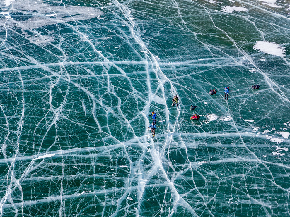 The photo was taken at ice skating journey on lake Baikal, Russia. Baikal in winter becomes the biggest ice rink in the world, fully covered with small and huge cracks, resembling spider's web. We enjoyed more than 300 kilometers of smooth (and sometimes rough) ice, skating from Listvyanka to Khuzhir whithin less than two weeks. On the photo you can see small figures of skaters dragging loaded sledges behind. Photograph by Evgeny Dubinchuk.