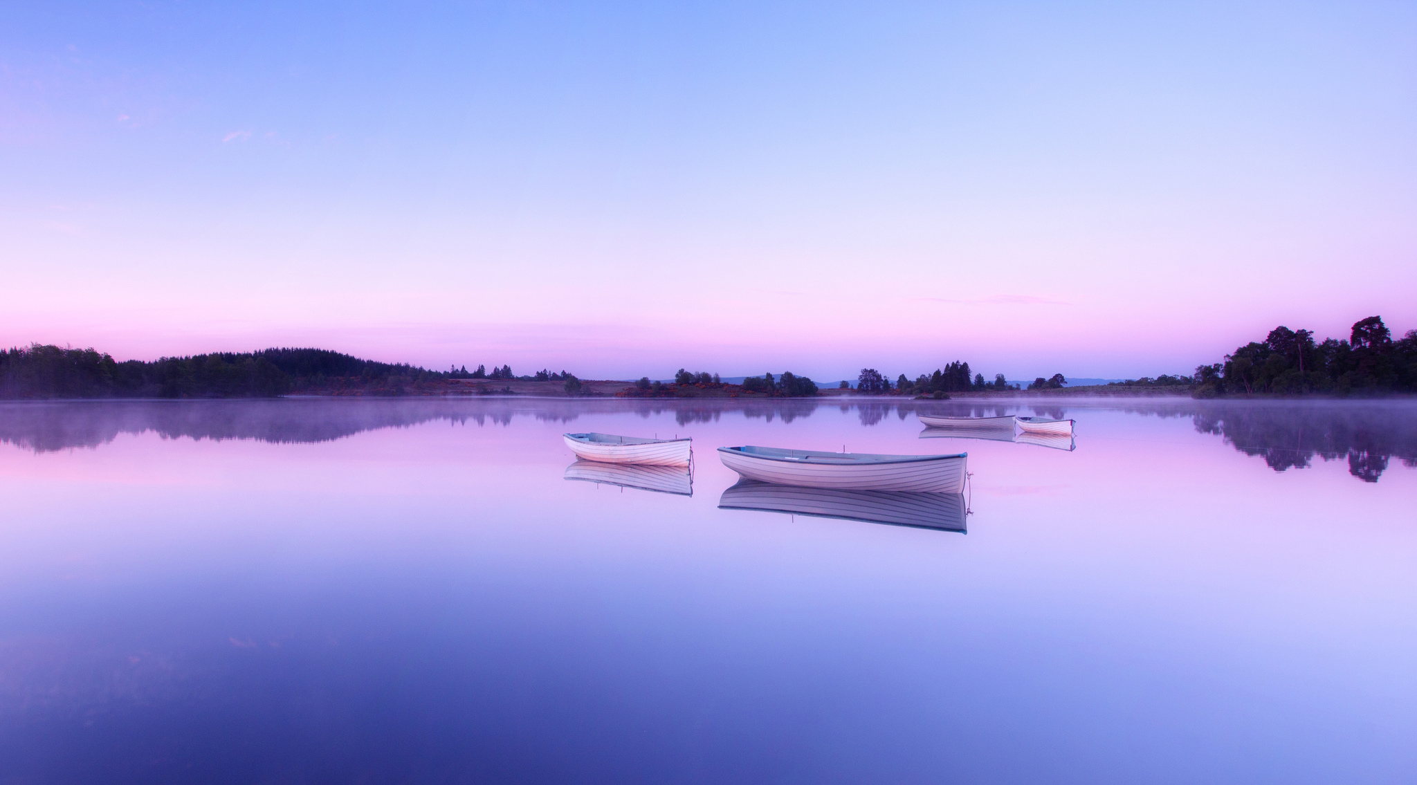 A mirror calm morning on Loch Rusky, Trossachs, Scotland with the wee boats from the local angling club sitting on the glass surface of the loch. Flickr - john mcsporran.