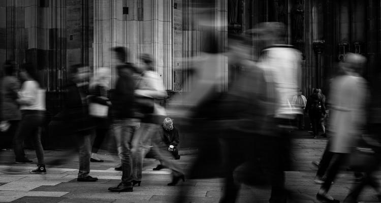 Seorang peminta-minta duduk di keramaian orang yang berlalu lalang. Jerman. Flickr -  richard overtoom.
